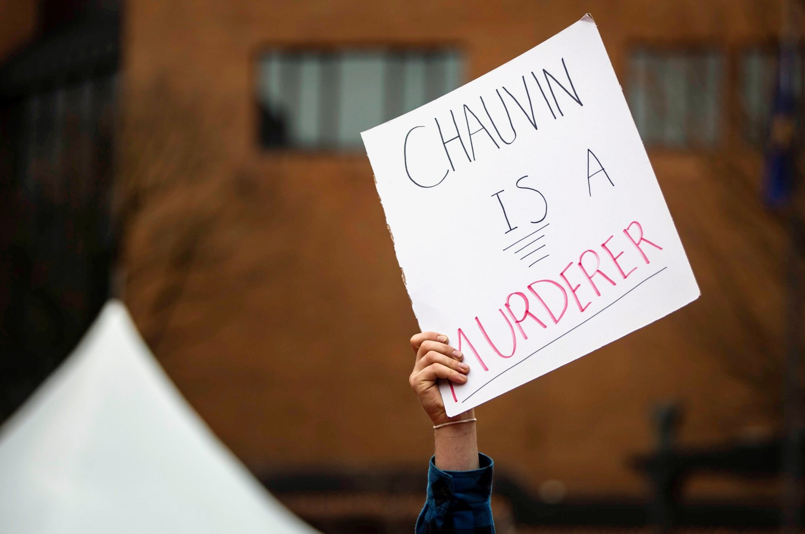 """A demonstrator holds a sign reading """"Chauvin is a murderer"""" during a march in Portland as jury selection begins in Minneapolis for the trial of Derek Chauvin, the former policeman accused of killing George Floyd, Oregon, U.S., March 8, 2021. (Reuters Photo)"""