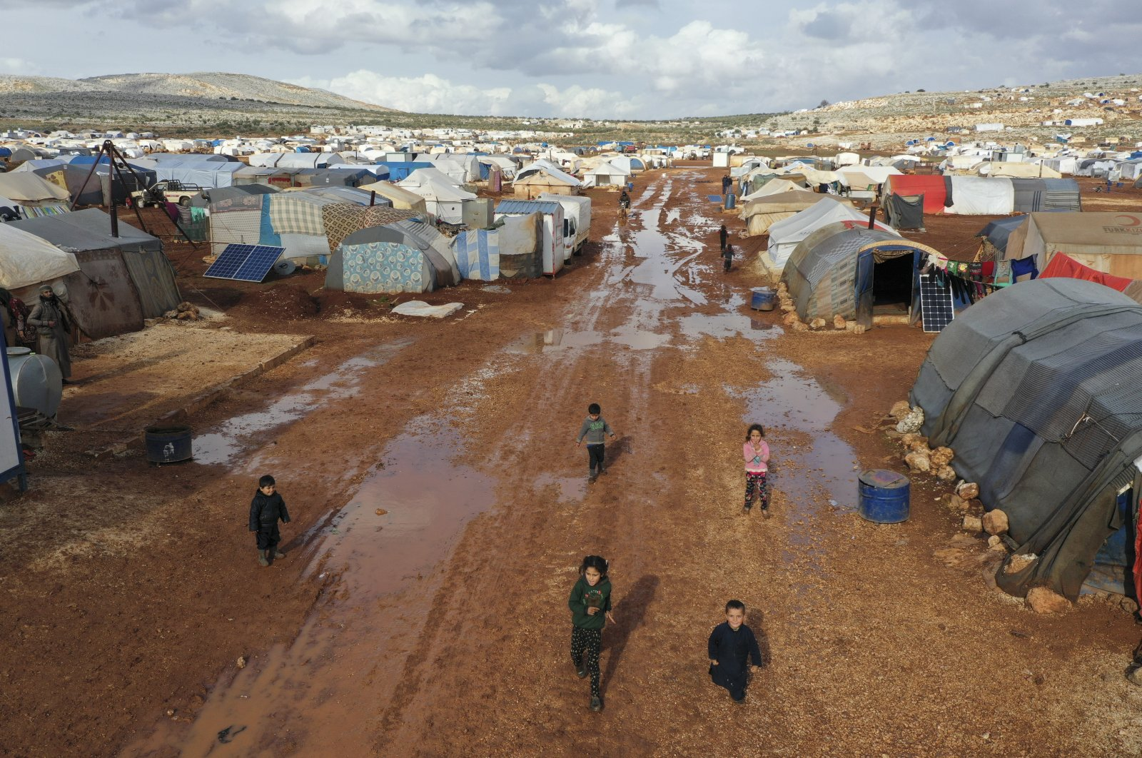Syrian refugees walk through a camp for displaced muddied by recent rains near the village of Kafr Aruq, in Idlib province, Syria, Jan. 28, 2021. (AP)