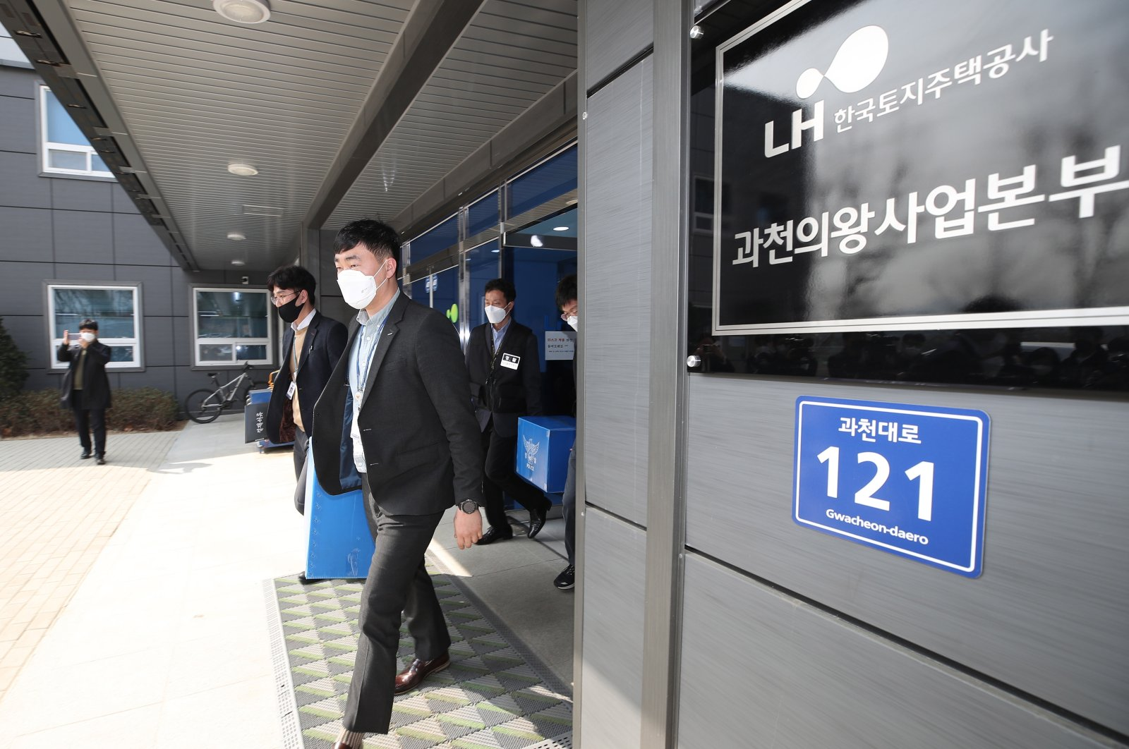 Police investigators carry boxes containing confiscated items out of an office of the state-run Korea Land and Housing Corp. (LH) in Gwacheon, just south of Seoul, South Korea, March 9, 2021. (EPA Photo)