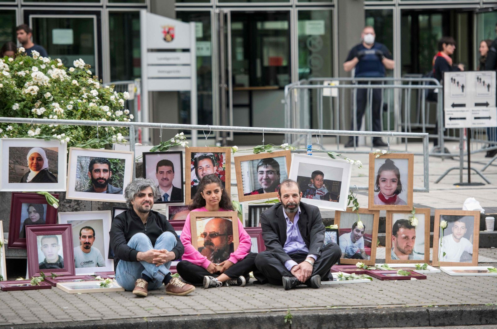 Syrian campaigner Wafa Mustafa (C) holding a picture of her father as she sits beside co-plaintiff, Syrian Oscar-nominated filmmaker Feras Fayyad (L), and Syrian human rights lawyer Anwar al-Bunni (R), in front of pictures of victims of the Syrian regime, during a protest outside the trial, in Koblenz, western Germany, June 4, 2020. (AFP)