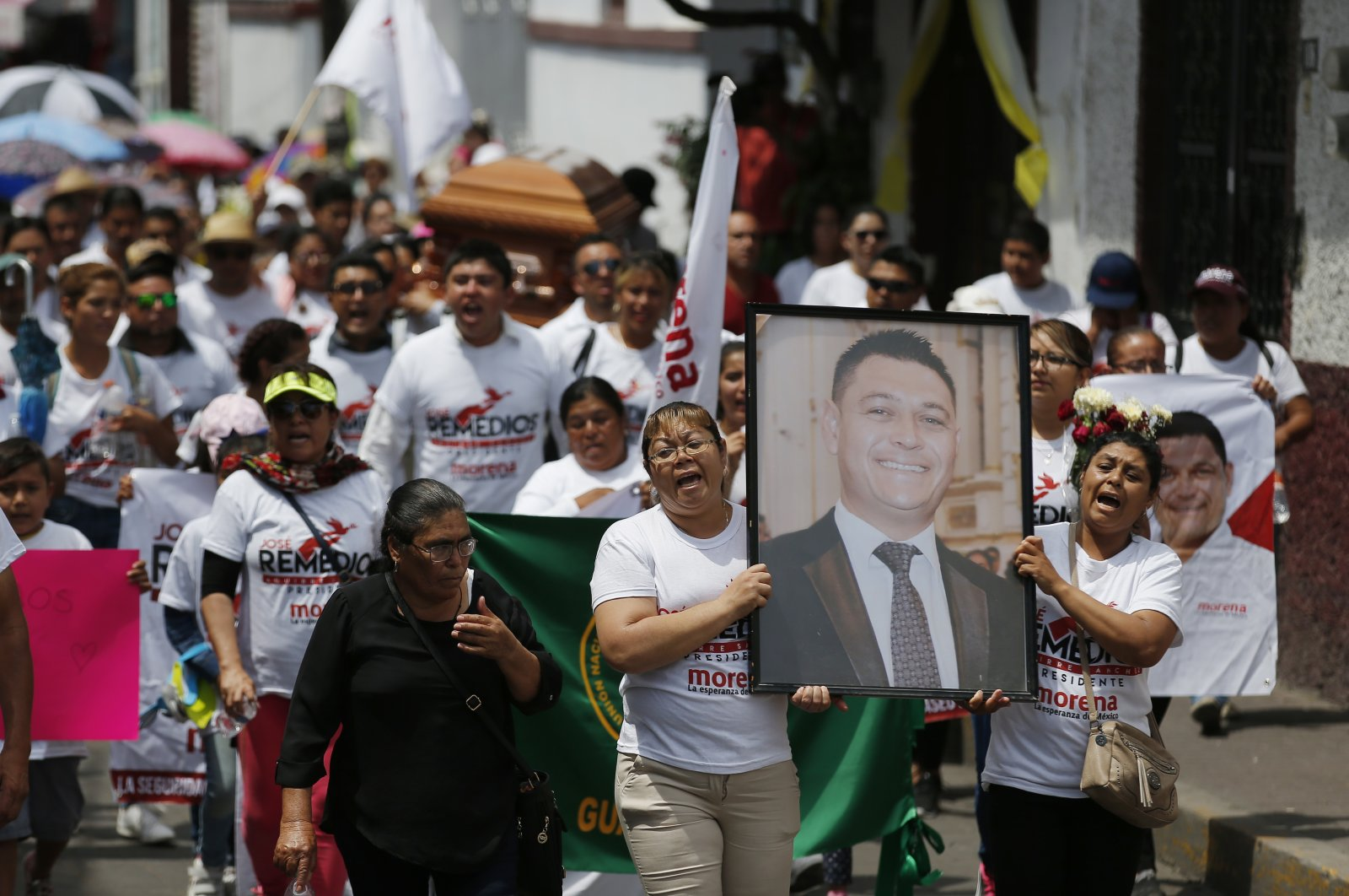 Women carry a photo of the late Jose Remedios Aguirre, a mayoral candidate who was shot in broad daylight two days prior, during his funeral procession in Apaseo El Alto, Mexico, May 13, 2018. (AP Photo)
