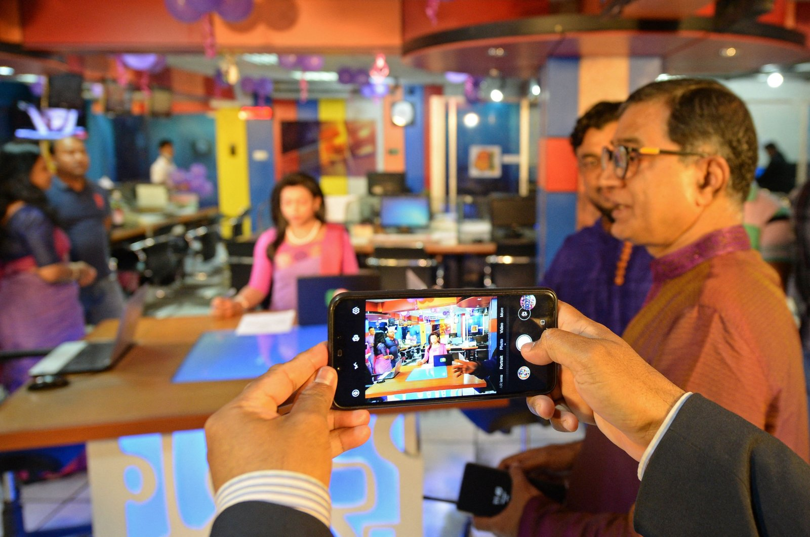 A co-worker of Tashnuva Anan Shishir who claims to be Bangladesh's first transgender television news presenter takes her photograph using a mobile phone at a news studio in Dhaka on March 8, 2021. (AFP Photo)