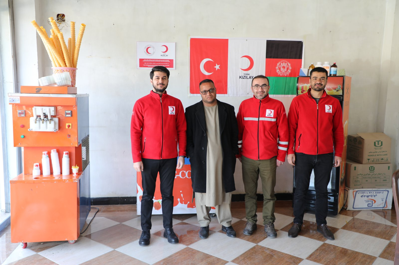 Employees of the Turkish Red Crescent and an Afghan returnee pose in the newly opened ice cream shop, Kabul, March 7, 2021. (AA Photo)