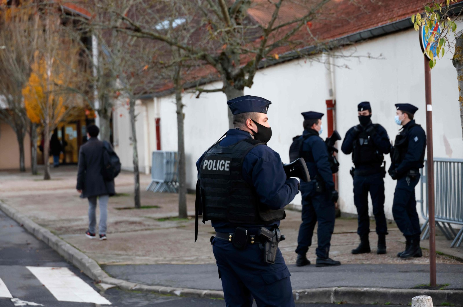 French CRS (Compagnies Republicaines de Securite) police officers stand near the entrance of Le Bois d'Aulne middle school where pupils return to school after the holidays, two weeks after a teacher was decapitated by an attacker, Conflans-Sainte-Honorine, northwest of Paris, France, Nov. 3, 2020. (AFP Photo)