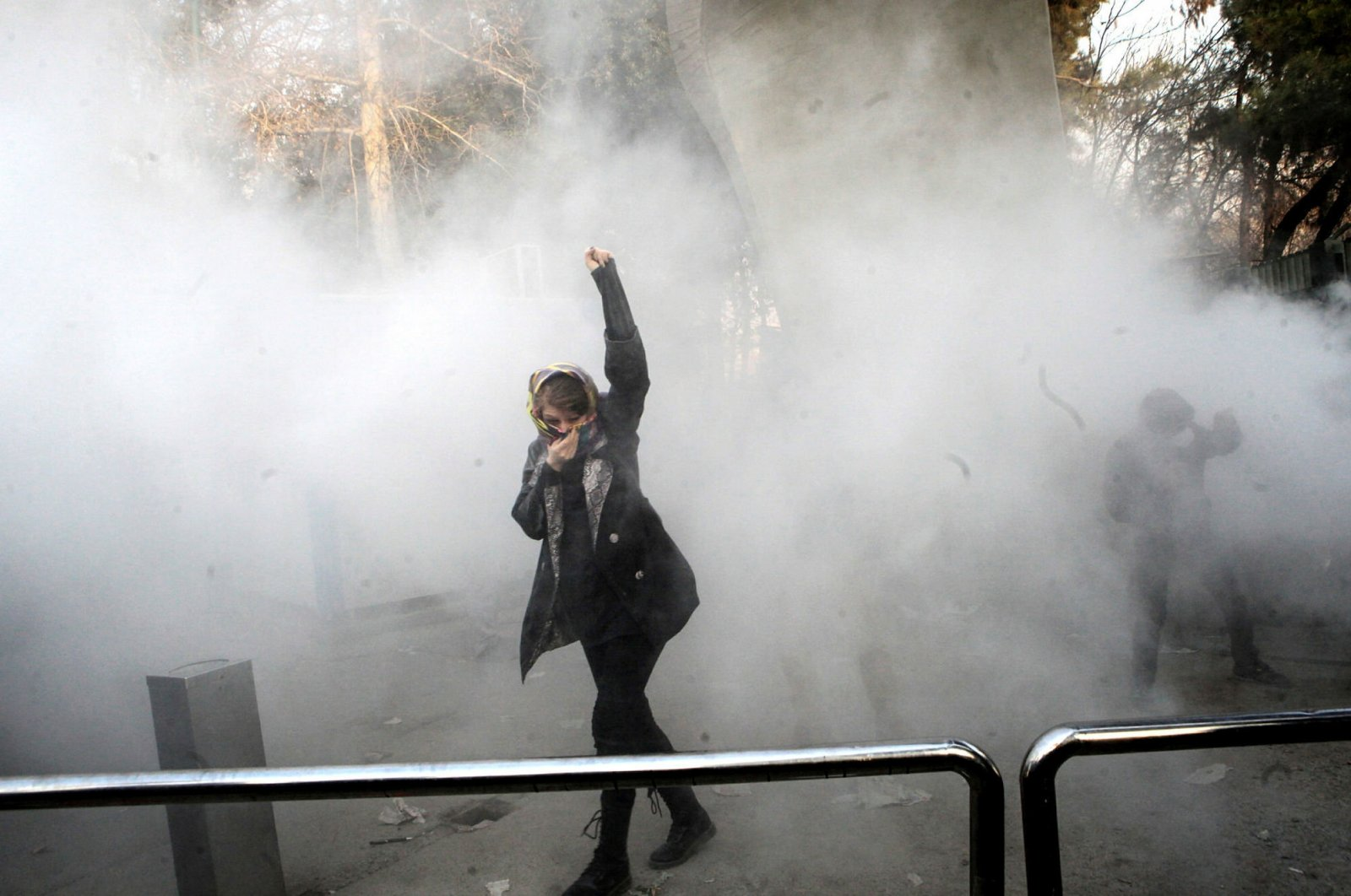 A woman raises his fist amid smoke during an anti-government protest in Iran. (Archive Photo)
