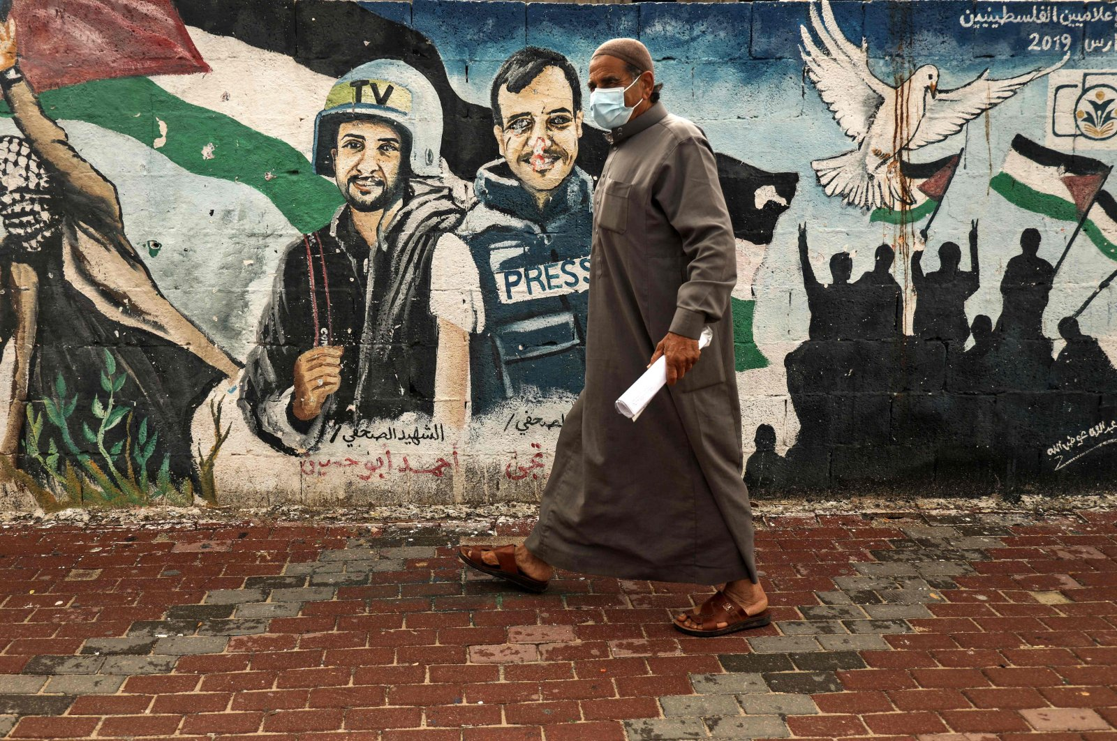 A Palestinian man wearing a face mask walks past a mural of journalists killed in 2014 between Hamas and Israel, in the Gaza Strip, March 4, 2021. (AFP Photo)