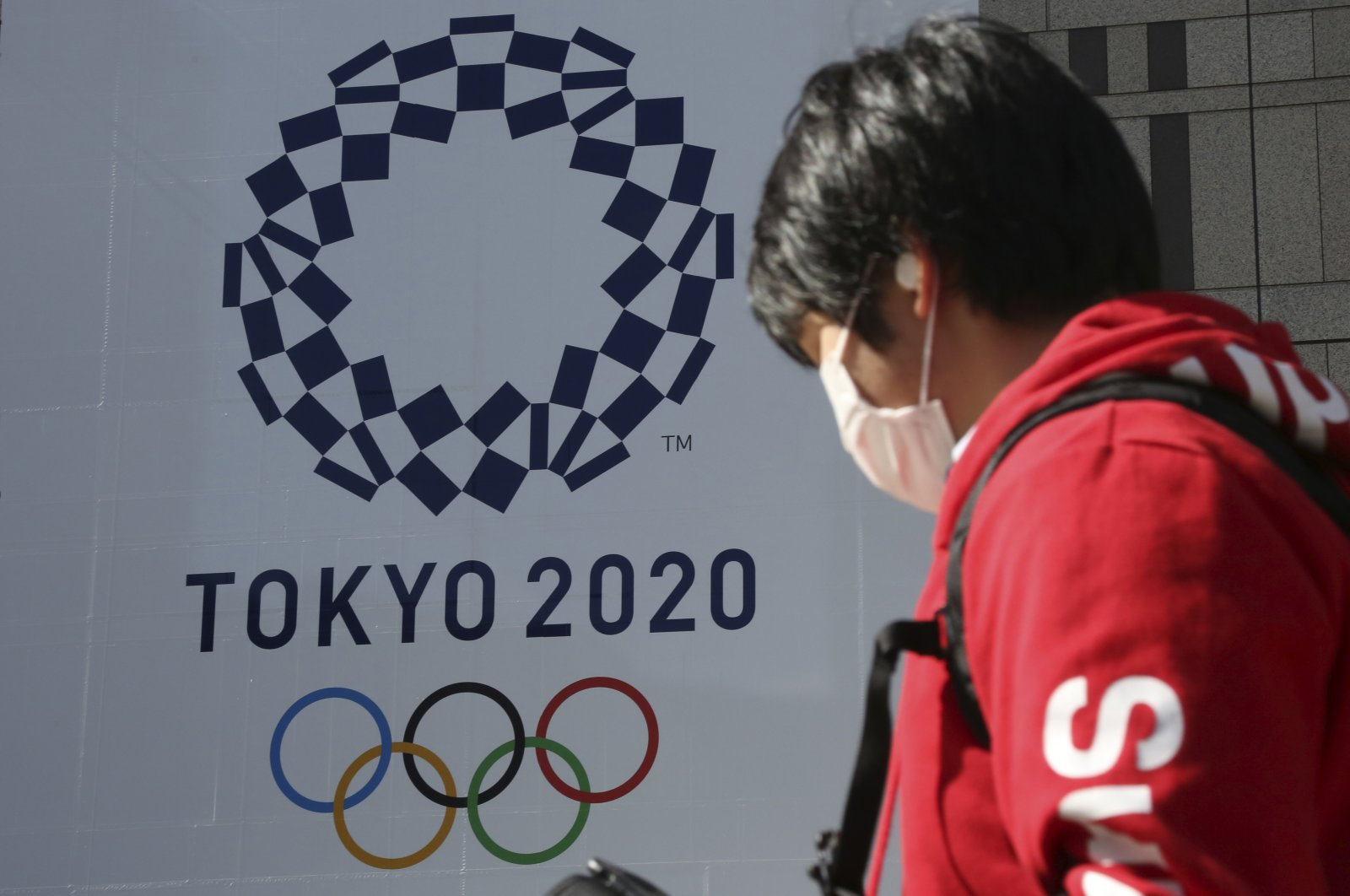 A man in a protective face mask walks by the logo of the Tokyo Olympics, in Tokyo, Japan Feb. 17, 2021. (AP Photo)