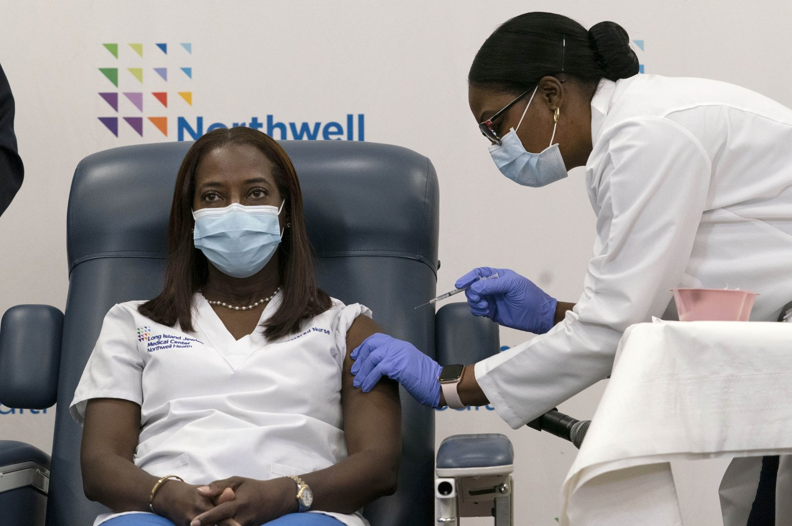 In this Dec. 14, 2020, file photo, Sandra Lindsay (L), a nurse at Long Island Jewish Medical Center, is inoculated with the Pfizer-BioNTech COVID-19 vaccine by Dr. Michelle Chester, in the Queens borough of New York. (AP Photo)