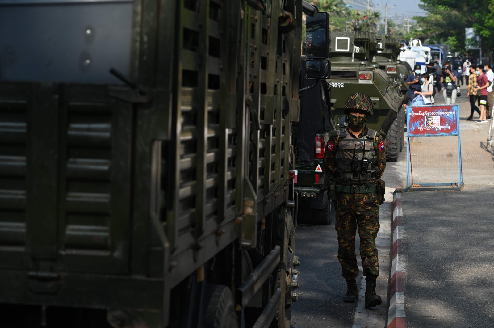 A soldier stands next to a line armoured vehicles outside the Central Bank of Myanmar, as people gathered to protest against the military coup, in Yangon on Feb. 15, 2021. (AFP Photo)