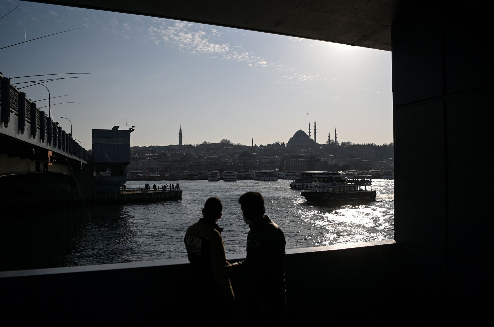 Two men look at the Golden Horn spanned by the Galata Bridge with the Süleymaniye mosque in background, at Eminönü district in Istanbul on March 9, 2021. (AFP Photo)