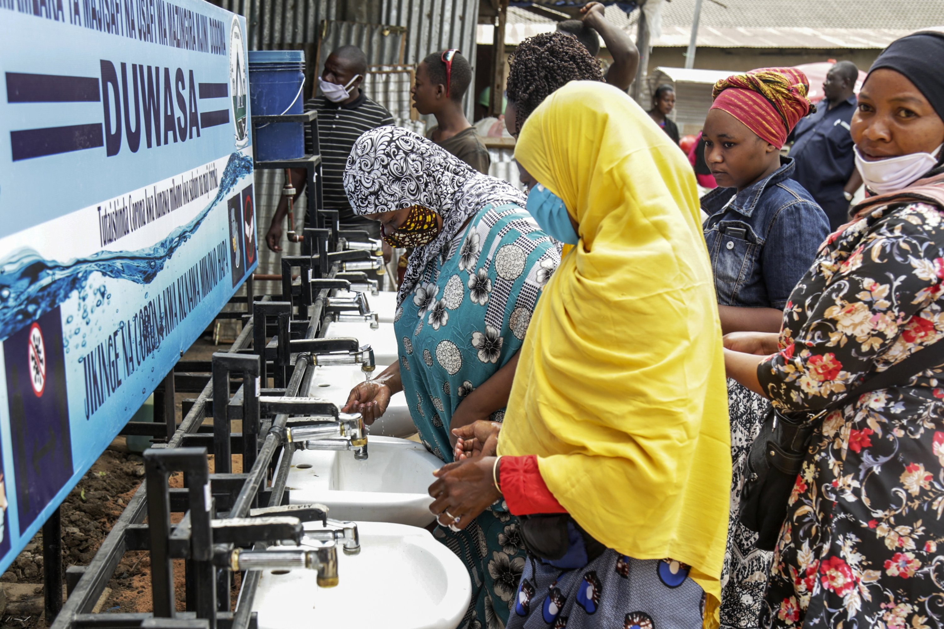 People use a hand-washing station installed for members of the public entering a market in Dodoma, Tanzania, May 18, 2020. (AP Photo)