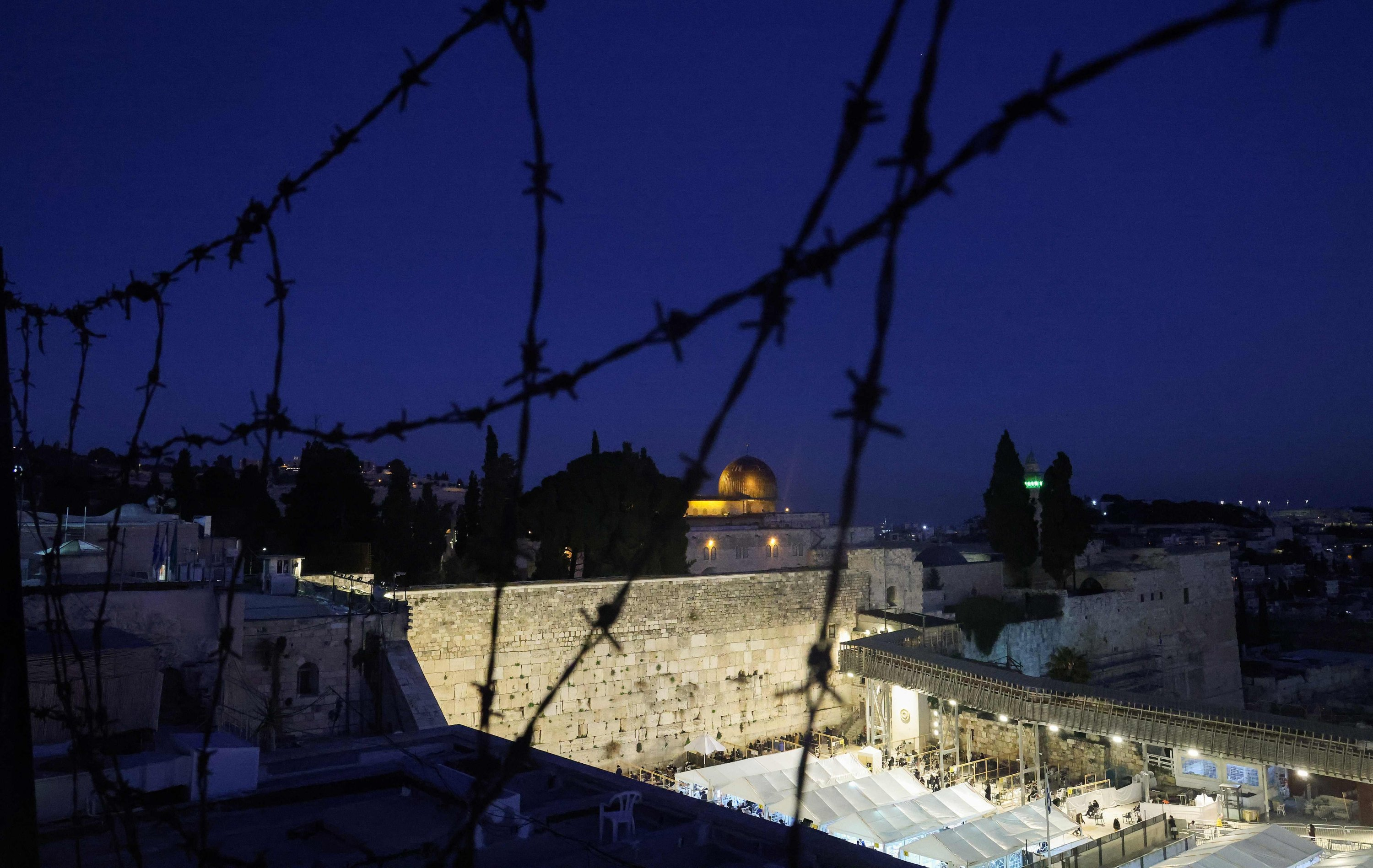A picture taken from a rooftop protected by barbed wire on February 13, 2021, shows the Western Wall and the Dome of the Rock, in the al-Aqsa mosque compound, in Jerusalem's Old City. (AFP Photo)