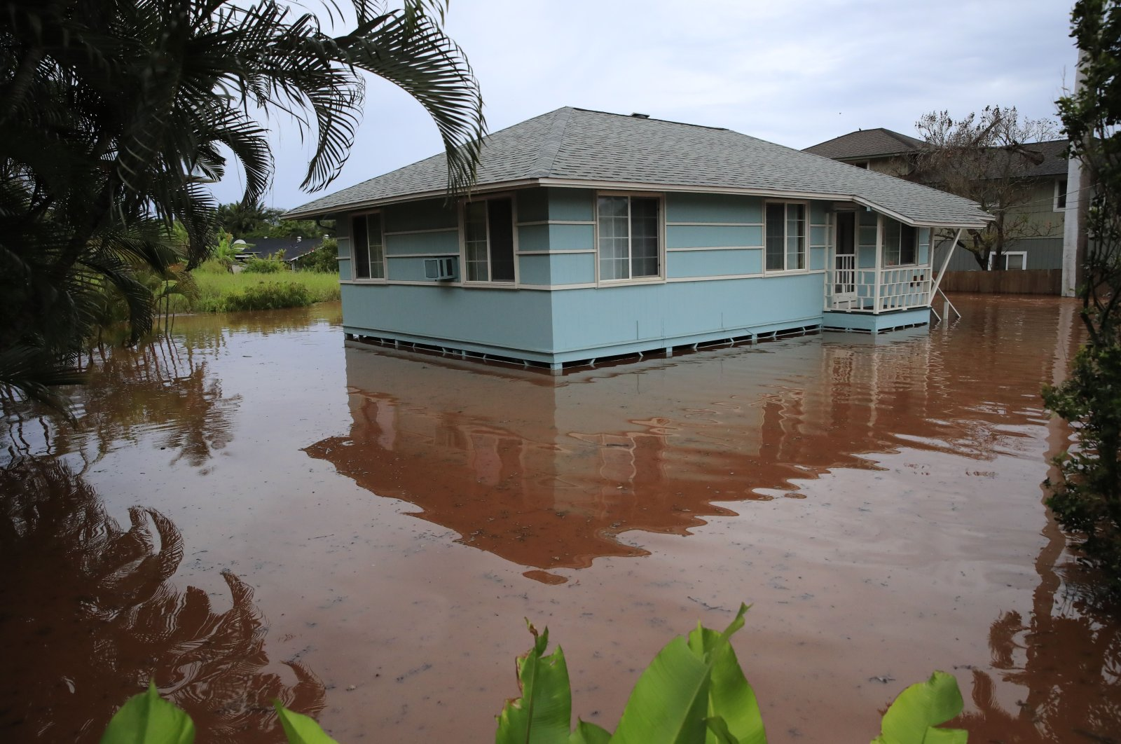 A house on Haleiwa Road is surrounded by floodwaters in Haleiwa, Hawaii, March 9, 2021. (AP Photo)