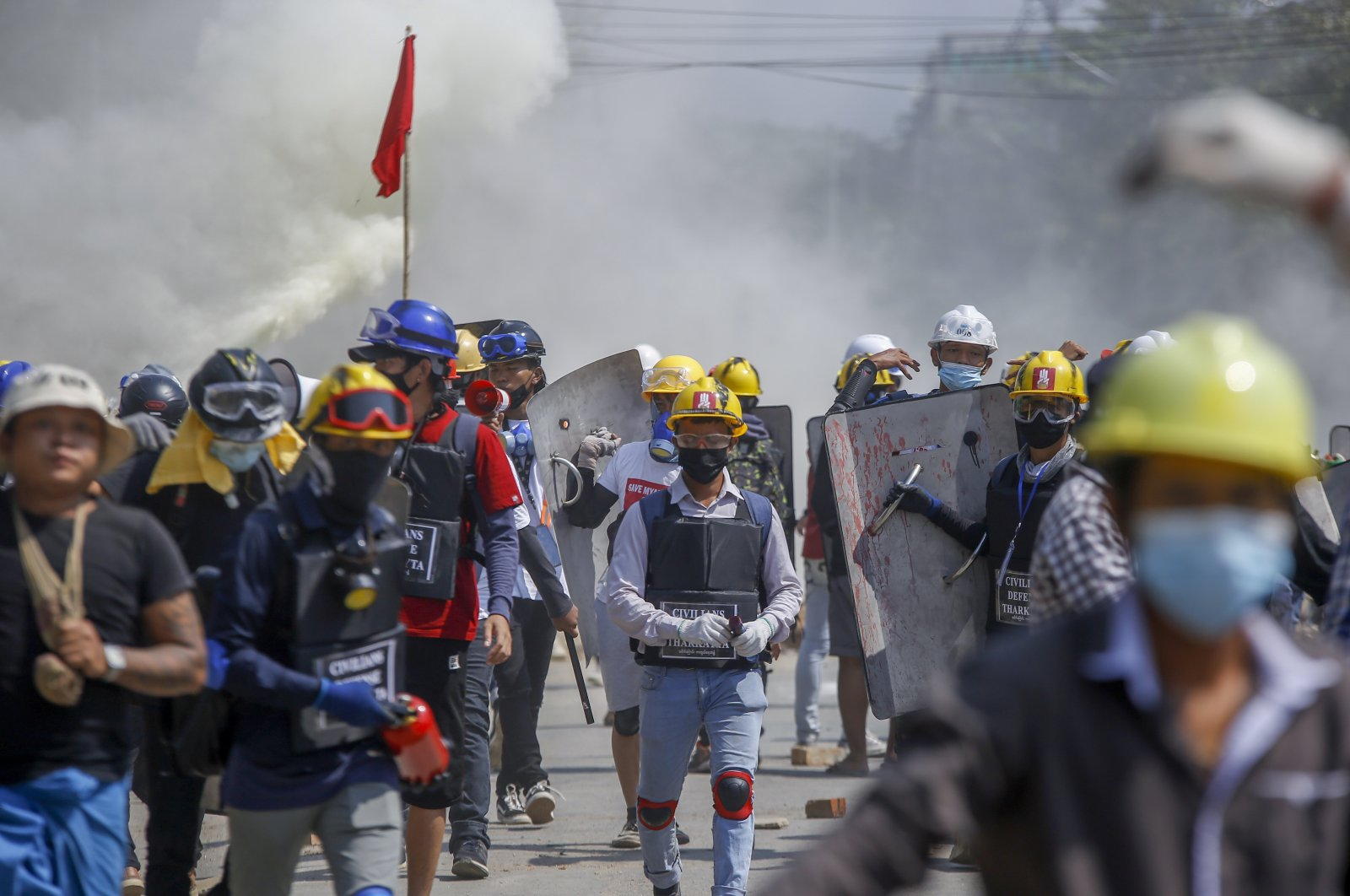 Anti-coup protesters retreat from the frontlines after discharging fire extinguishers toward a line of riot policemen in Yangon, Myanmar Wednesday, March 10, 2021. (AP Photo)