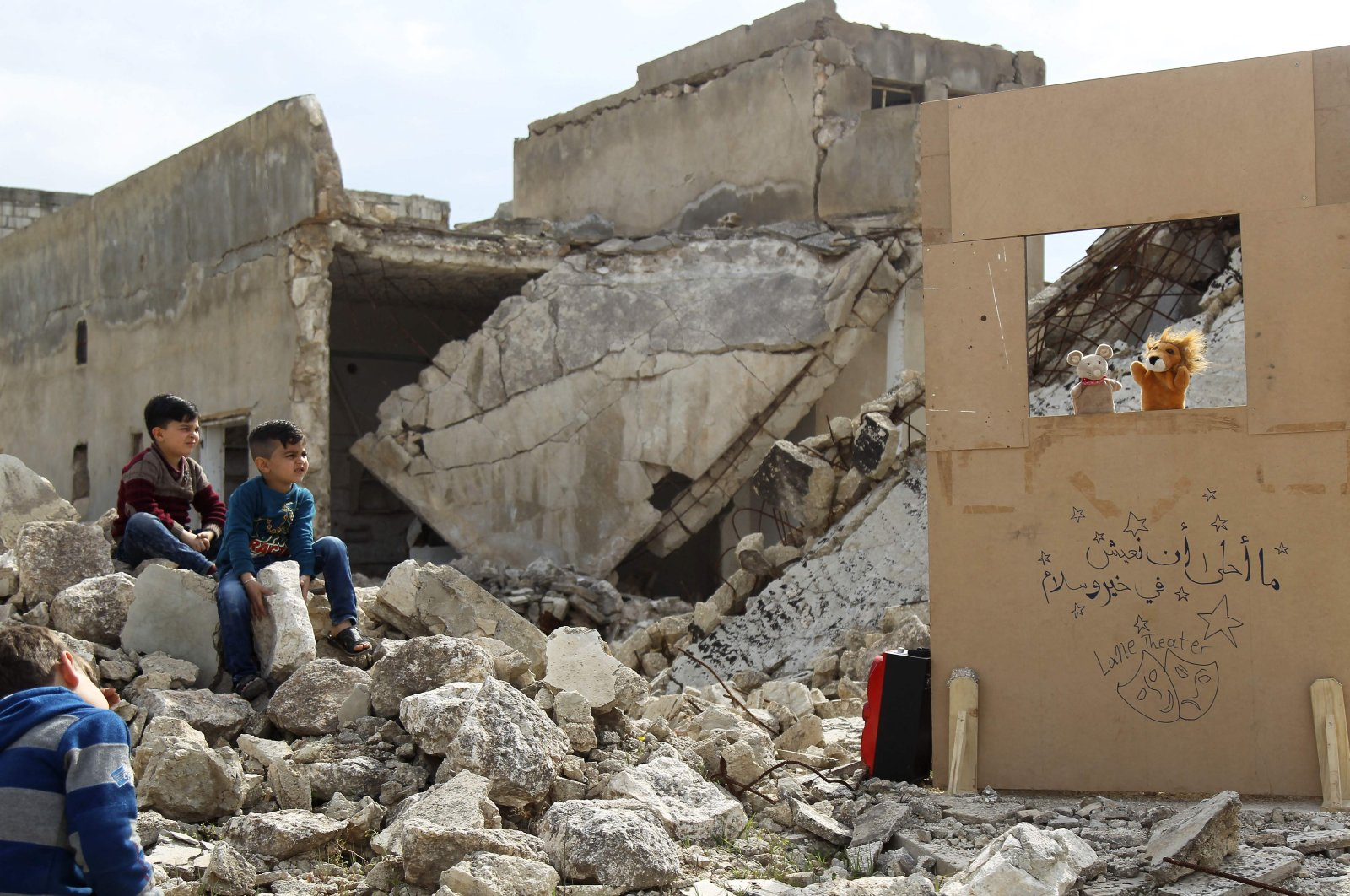 Children watch a puppet show performed by a Syrian actor, through a makeshift puppet theater set up among the rubble of collapsed buildings in the town of Saraqib in the opposition-held northern Idlib province, March 27, 2019. (AFP Photo)