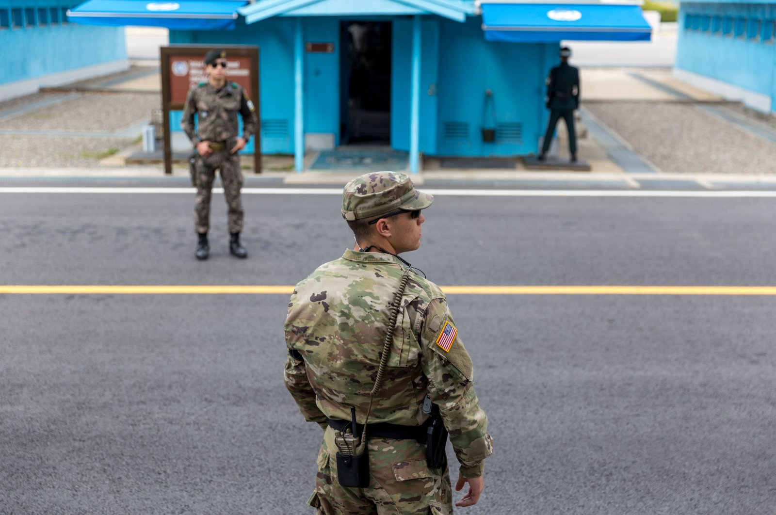U.S. Marine and two Republic of Korea (ROK) soldiers watching over the demilitarized zone (DMZ) at the Korean border, Joint Security Area, Kaesong, South Korea, April 22, 2017. (Shutterstock Photo)