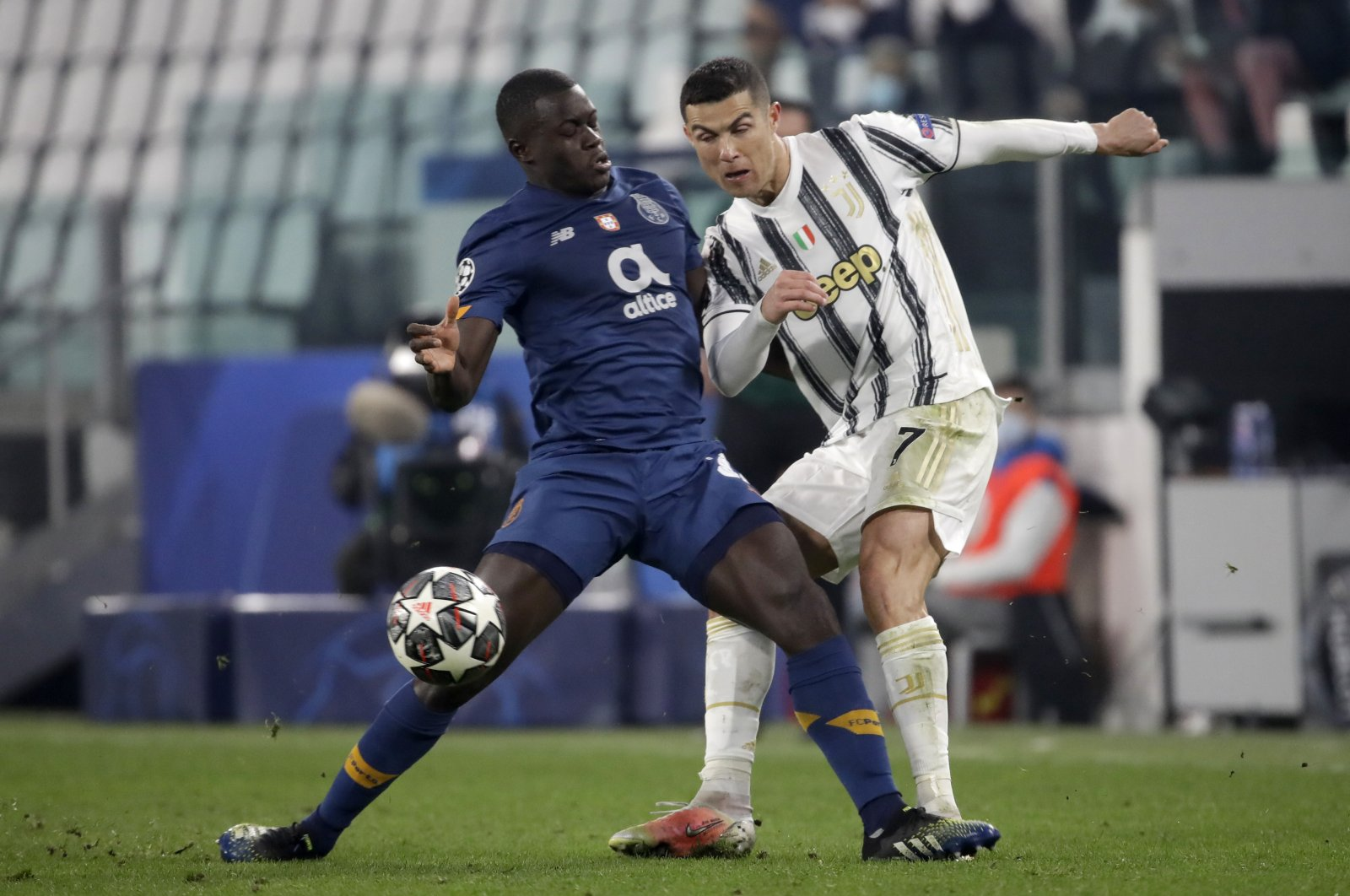 Porto's Malang Sarr (L) vies for the ball with Juventus' Cristiano Ronaldo during the Champions League round of 16, second leg match in Turin, Italy, March 9, 2021. (AP Photo)