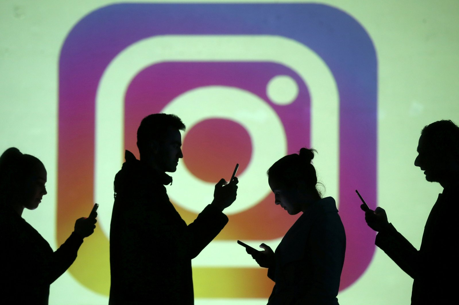 Silhouettes of mobile users are seen next to a screen projection of the Instagram logo in this picture illustration taken March 28, 2018. (REUTERS Photo)