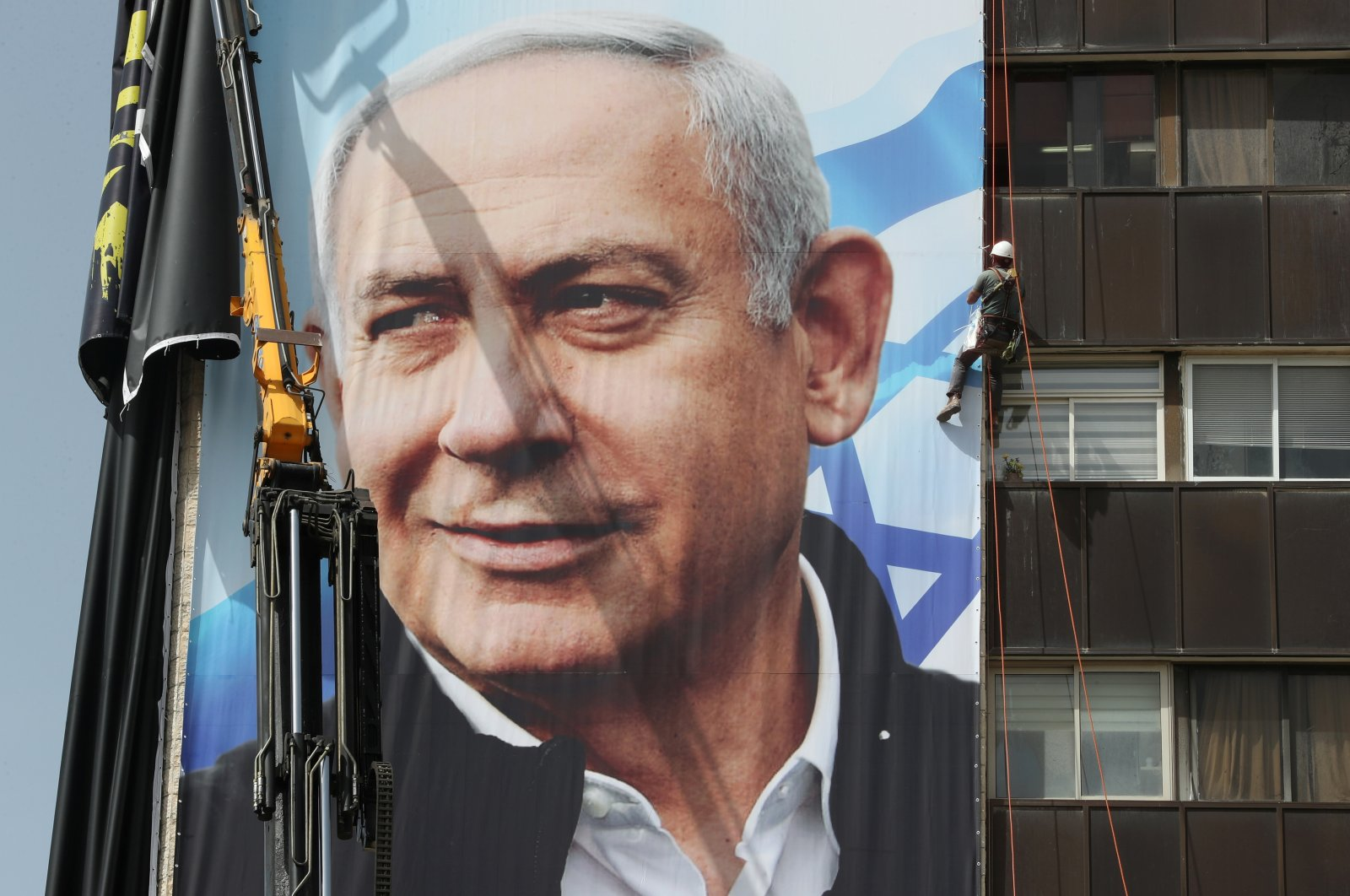 A laborer hangs a Likud Party election campaign banner depicting party leader Israeli Prime Minister Benjamin Netanyahu, ahead of a March 23 ballot, in Jerusalem, March 10, 2021. (Reuters Photo)