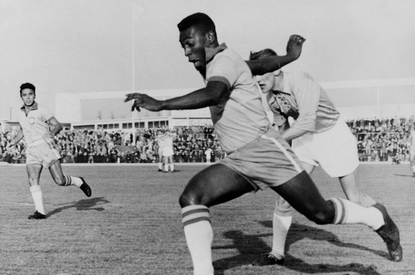 In this undated photo, Brazilian football legend Pele dribbles past a defender during a friendly match between Malmo and Brazil, in Malmo, Sweden. (AFP Photo)