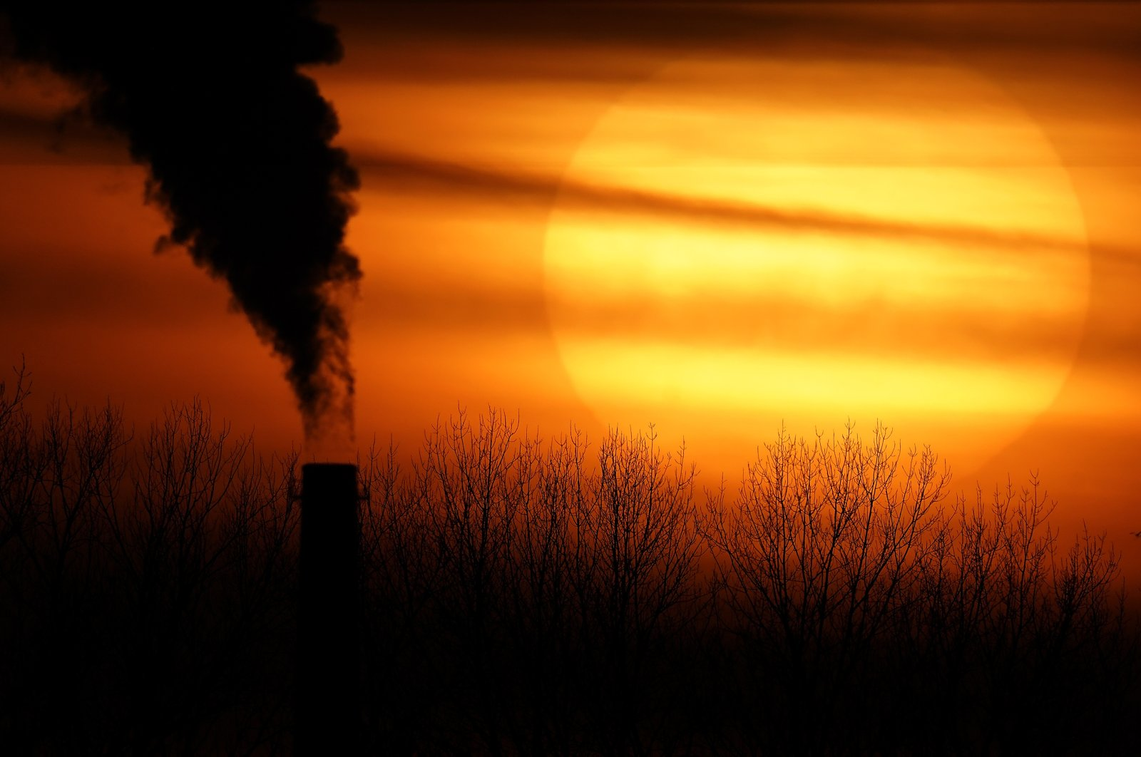 Emissions from a coal-fired power plant are silhouetted against the setting sun in Independence, Missouri, US, Feb. 1, 2021. (AP Photo)