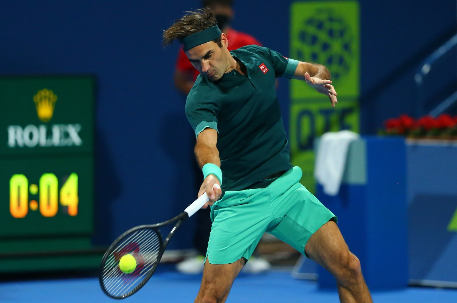 A handout photo made available by beIN Sports of Roger Federer of Switzelrand playing a forehand against Daniel Evans of Great Britain during their match at the Qatar Exxonmobil Open in Doha, Qatar, 10 March 2021. (EPA handout by beIN Sports)