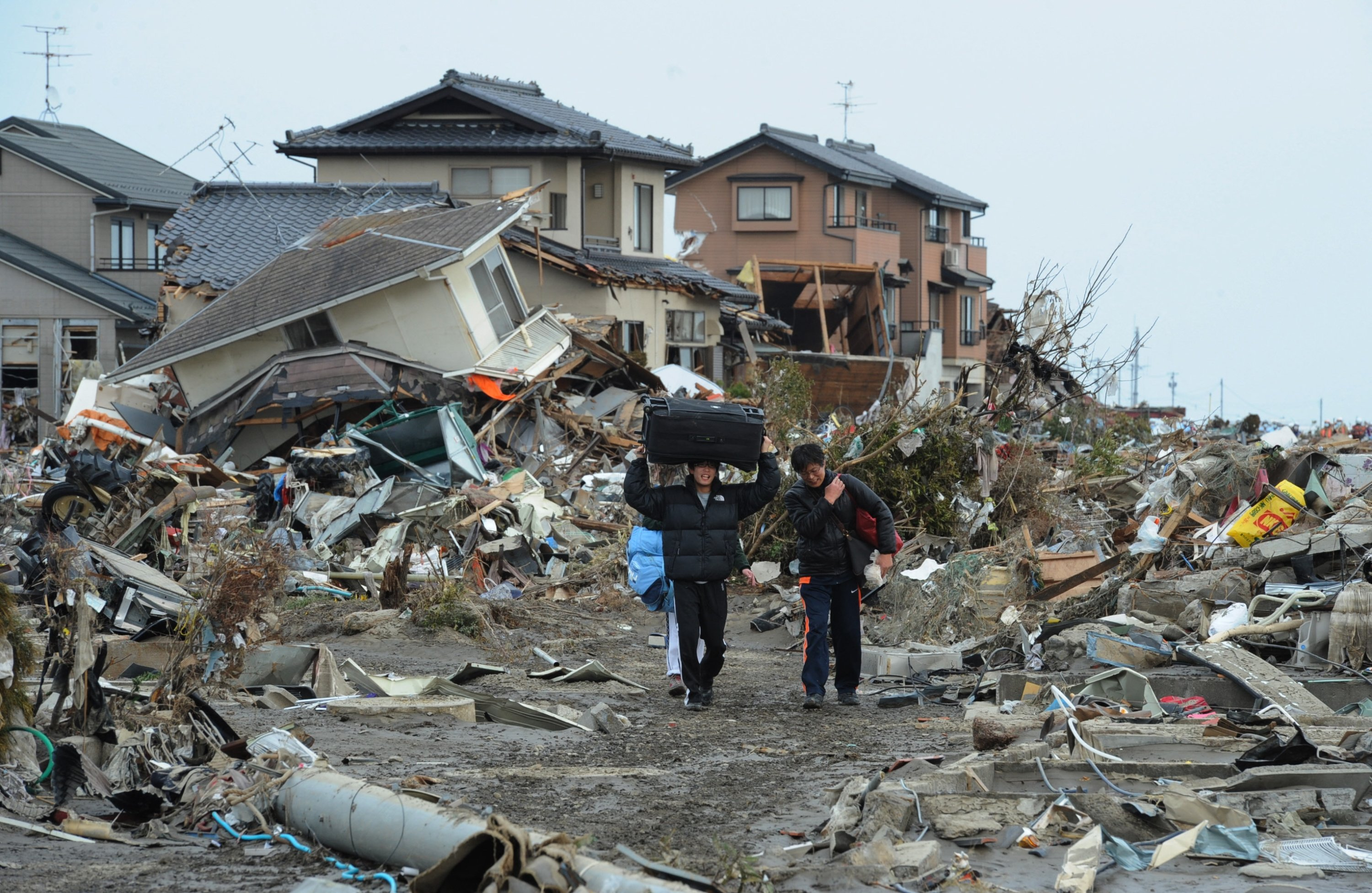 Residents carry belongings from tsunami devastated homes in Natori, Miyagi prefecture, in the wake of the 9-magnitude quake and tsunami which hit the region, Japan, March 14, 2011. (AFP)