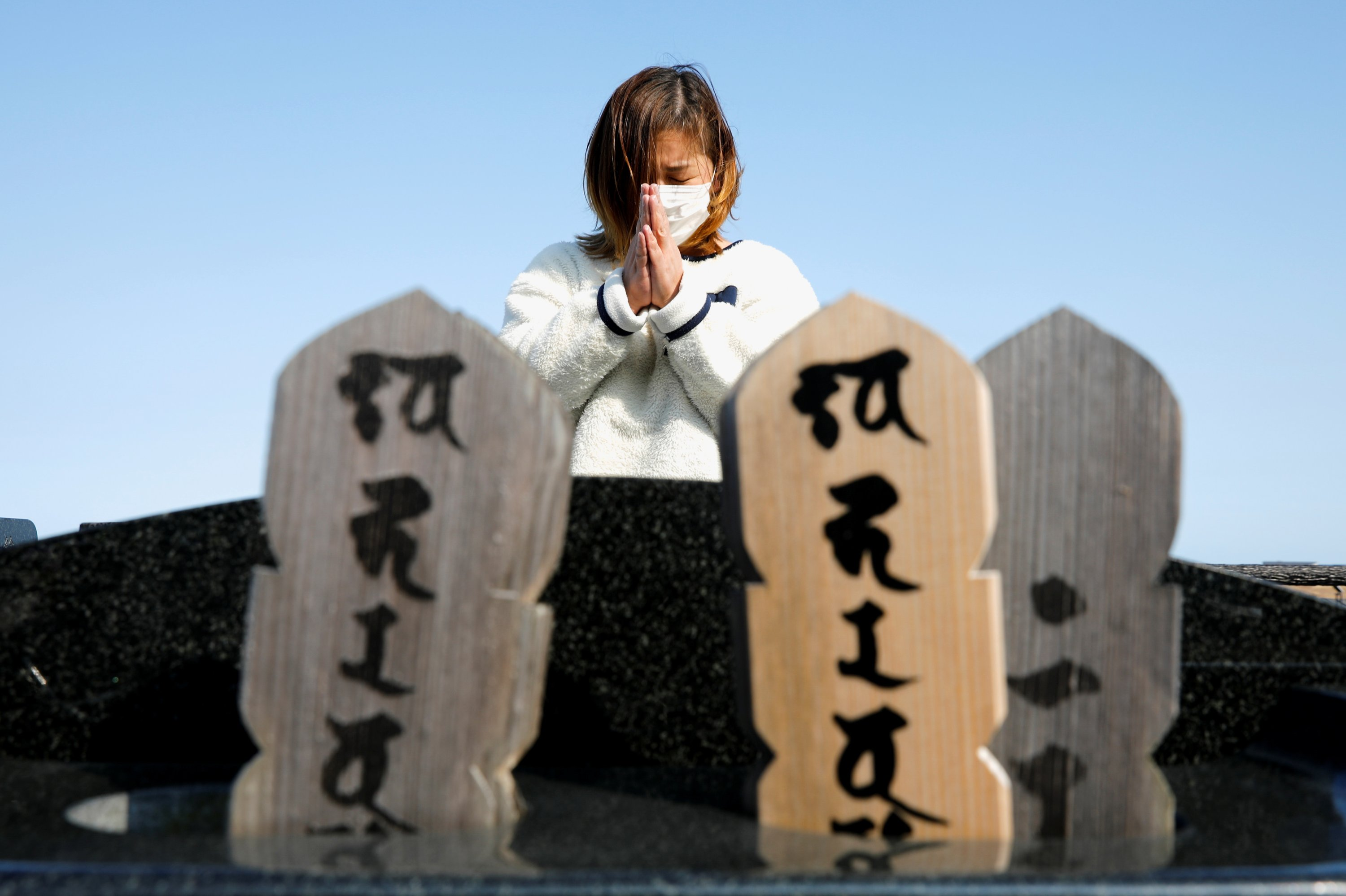 Harue Motoi, whose parents and younger brother died in 2011, prays in front of their grave during the 10th anniversary of the Fukushima disaster, in Namie, Fukushima prefecture, Japan, March 11, 2021. (Reuters)