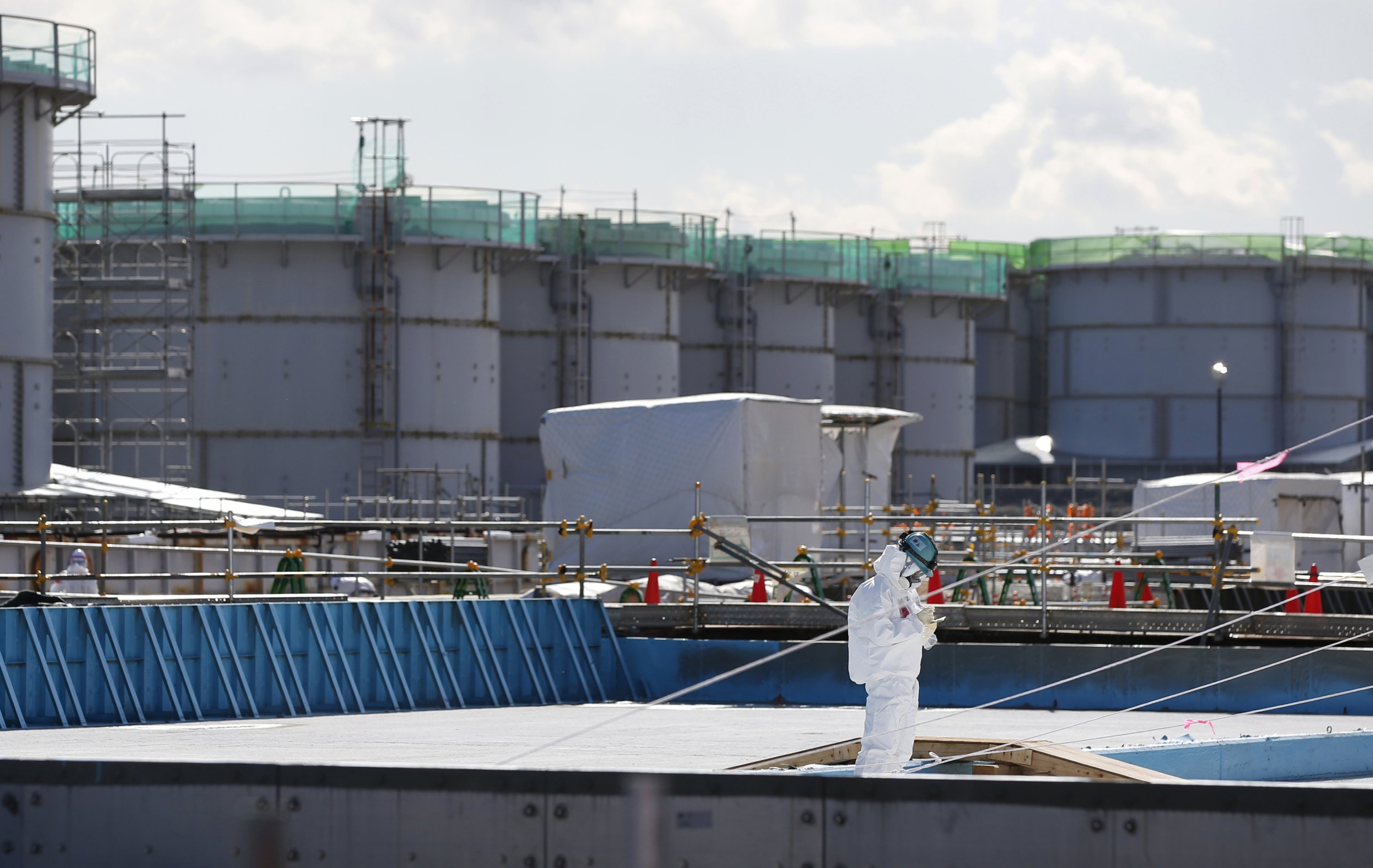 A worker, wearing a protective suit and mask, takes notes in front of storage tanks for radioactive water at the tsunami-crippled Fukushima Daiichi nuclear power plant in Okuma town, Fukushima Prefecture, northeastern Japan, Feb. 16, 2016. (AP)