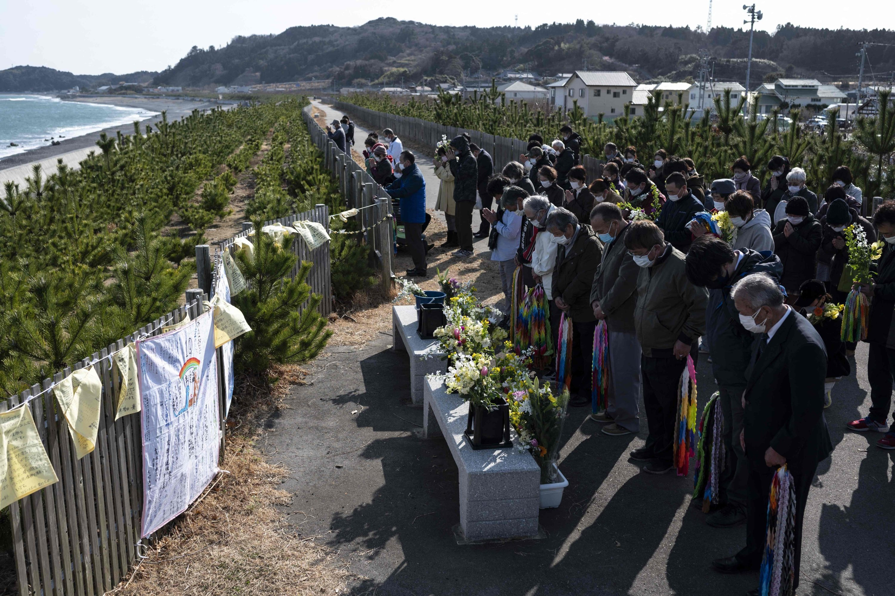 People observe a minute's silence in front of the sea in Hisanohama, marking the 10th anniversary of the 9 magnitude earthquake, Fukushima prefecture, Japan, March 11, 2021. (AFP)