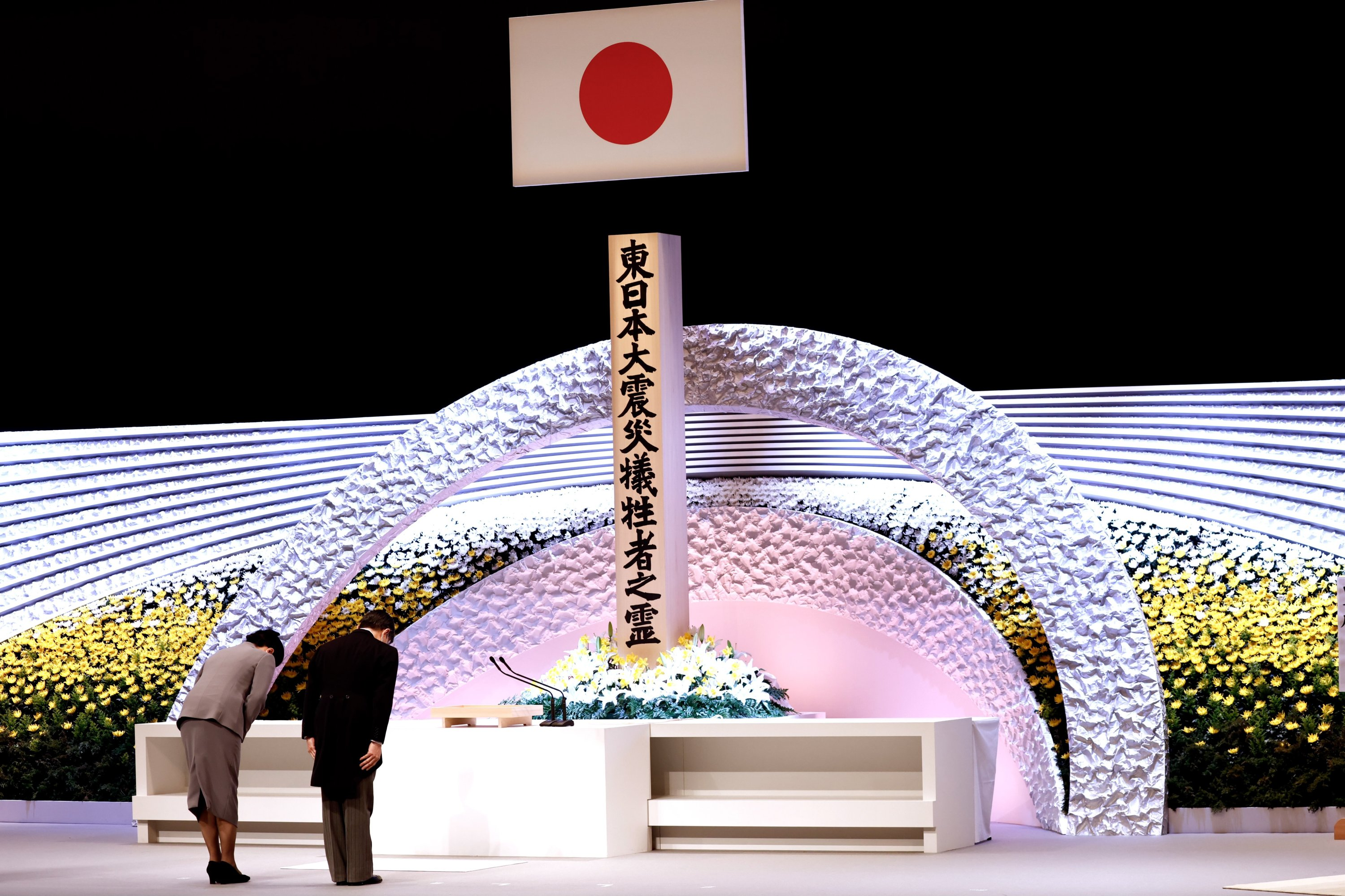 Japan's Emperor Naruhito (R) and Empress Masako (L) bow in front of the altar for victims of the March 11, 2011 earthquake and tsunami at the national memorial service in Tokyo, Japan, March 11, 2021. (EPA)
