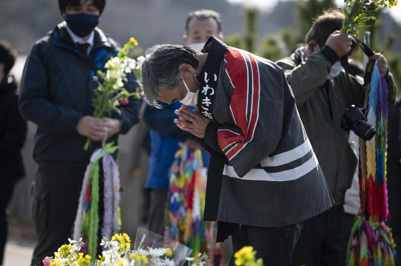 A man prays in front of the sea in Hisanohama, Fukushima prefecture on the 10th anniversary of the 9.0 magnitude earthquake which triggered a tsunami and nuclear disaster, Japan, March 11, 2021. (AFP)