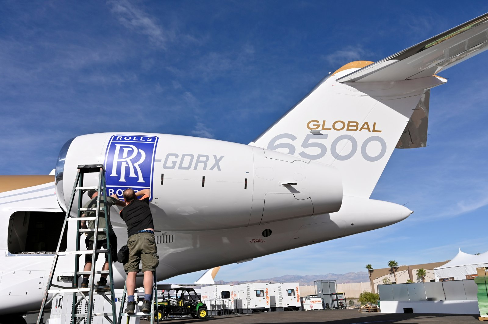 Workers apply a Rolls-Royce decal to the engine of a Bombardier Global 6500 business jet at the Bombardier booth at the National Business Aviation Association (NBAA) exhibition in Las Vegas, Nevada, U.S., Oct. 21, 2019. (Reuters)