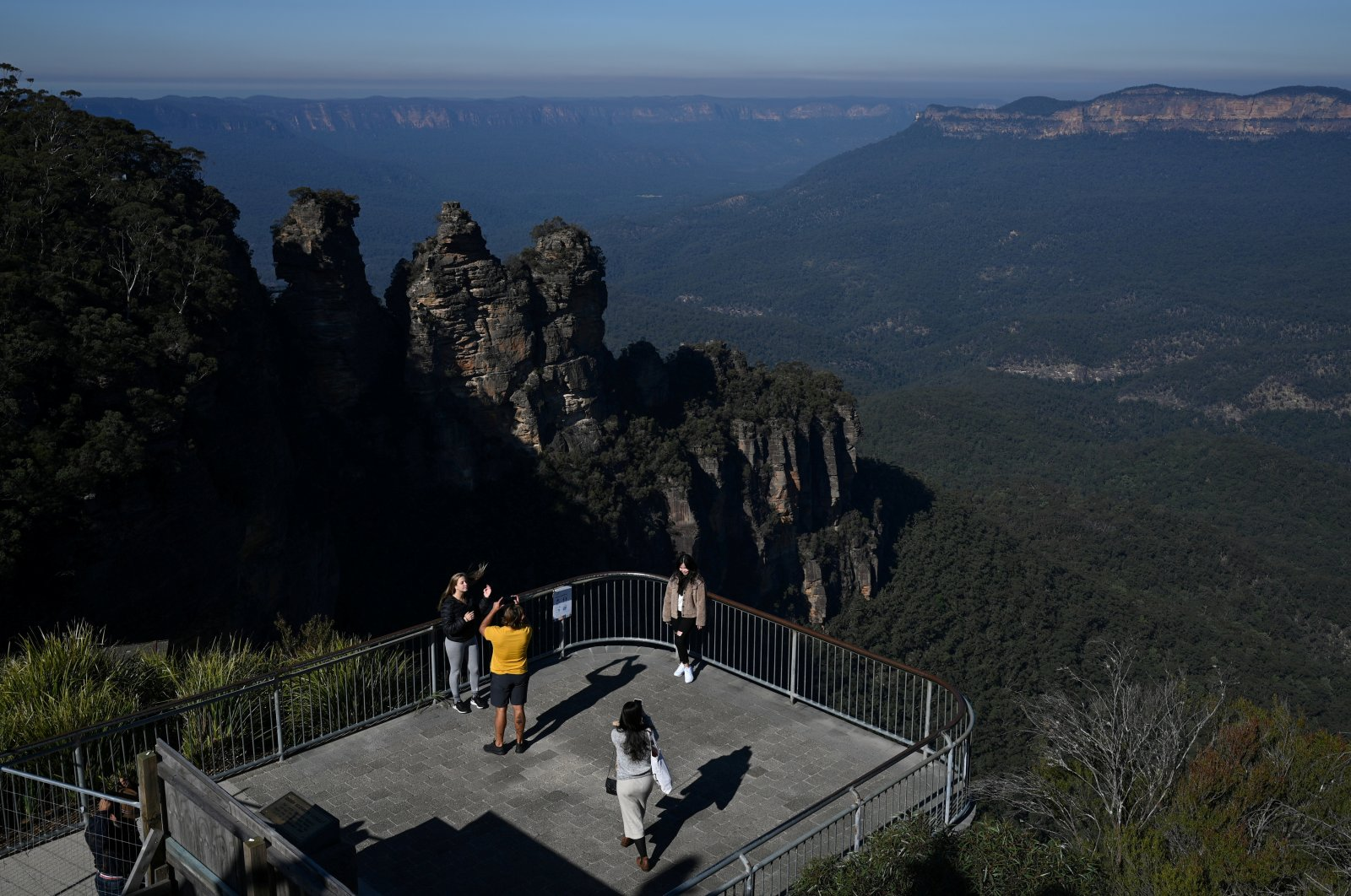 Tourists pose for photos at the Three Sisters rock formation in the Blue Mountains National Park in the wake of regional travel reopening as COVID-19 restrictions are eased, New South Wales, Katoomba, Australia, June 5, 2020.  (Reuters)