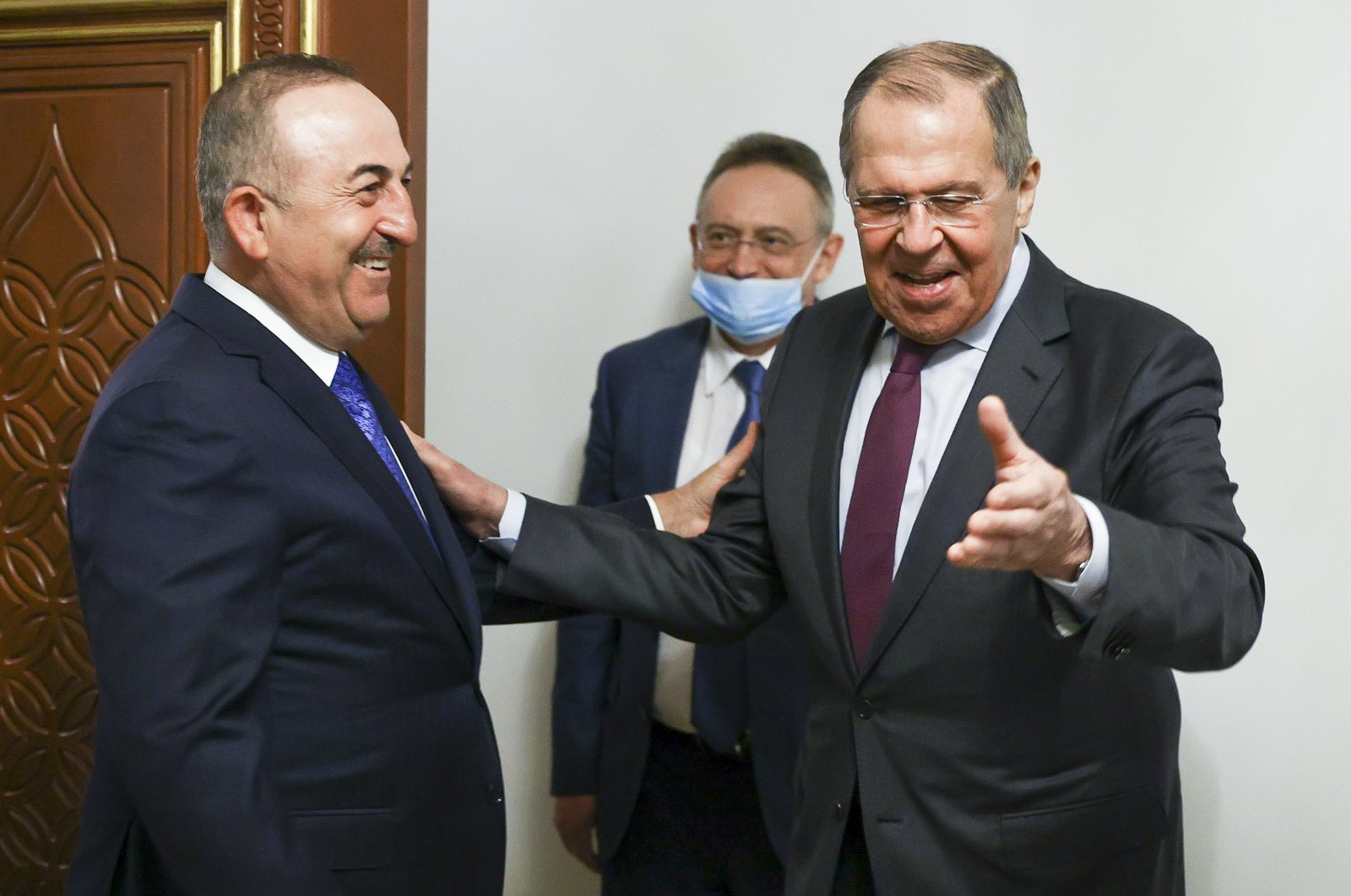 Russian Foreign Minister Sergey Lavrov (R) welcomes Turkish Foreign Minister Mevlut Cavusoglu for the talks at an airport outside Doha, Qatar, March 10, 2021. (Russian Foreign Ministry Press Service via AP)