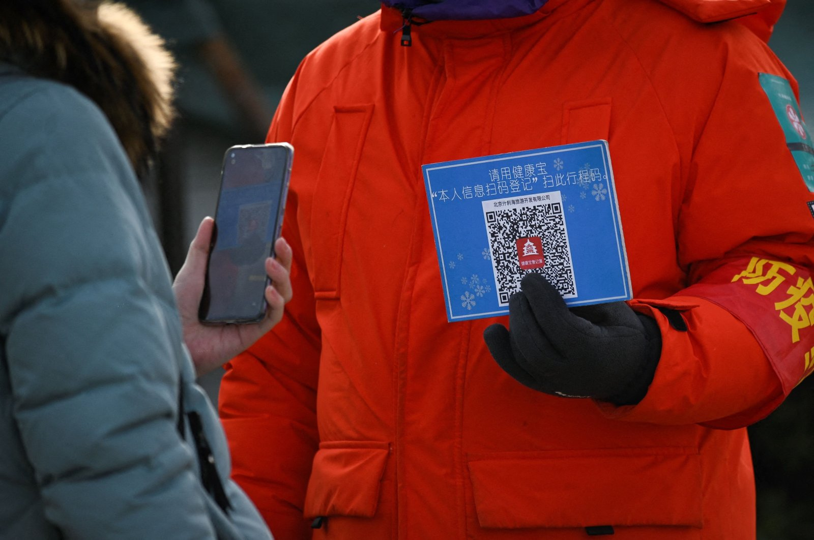 A woman using her mobile phone to scan a QR code for health registration before entering an outdoor ice rink in Beijing, China, Jan 12, 2021. (AFP Photo)