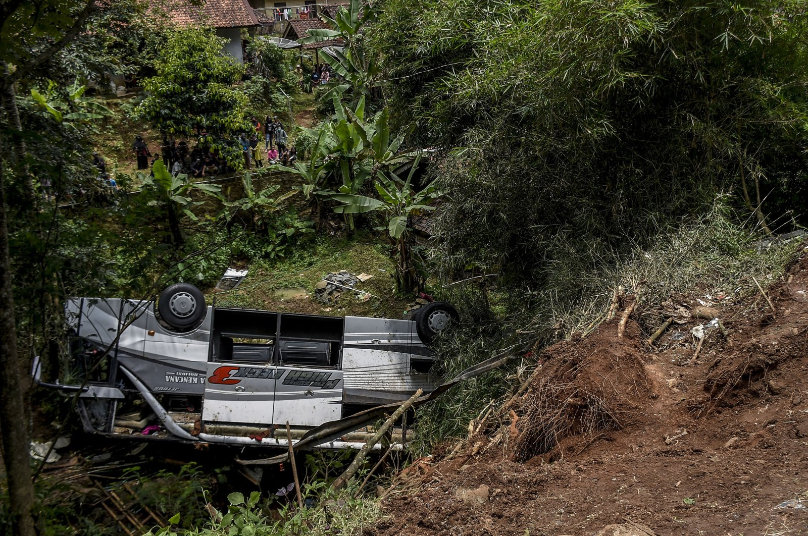 Residents inspect the wreckage of a bus that plunged into a ravine in Sumedang West Java,  Indonesia, March 11, 2021. (AP Photo)