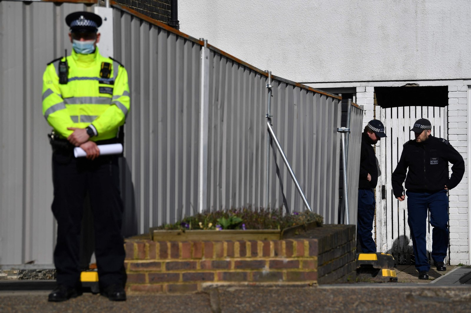 A police officer stands guard at a temporary police barrier around the home of a murder suspect after the discovery of human remains on the grounds of Great Chart Golf and Leisure near Ashford, Deal, Kent, England on March 11, 2021. (AFP Photo)