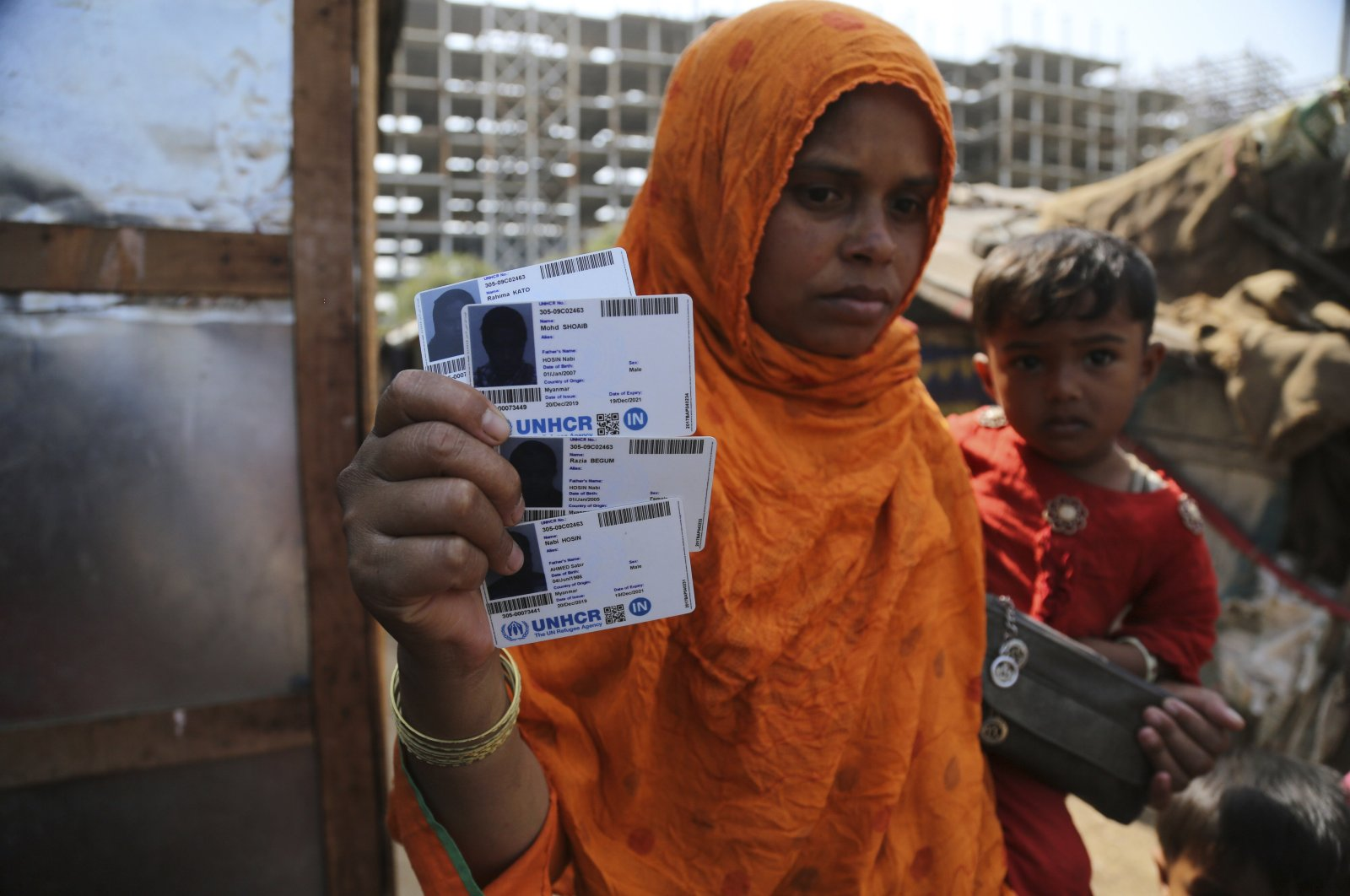 Rahima kato, a Rohingya woman displays identity cards of her family members issued by United Nations High Commissioner for Refugees (UNHCR) at their makeshift camp on the outskirts of Jammu, India, March 9,2021. (AP Photo)