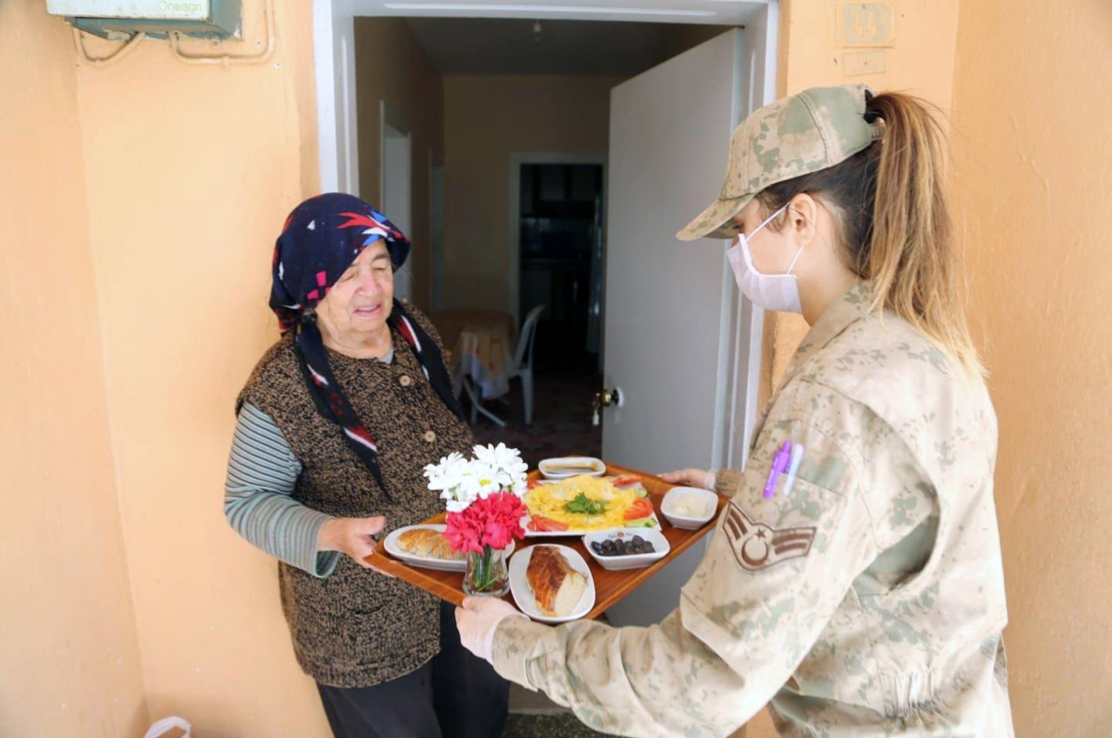 A military officer, a member of a Vefa group, delivers breakfast to an elderly woman, in Tunceli, eastern Turkey, April 14, 2020. (AA PHOTO)