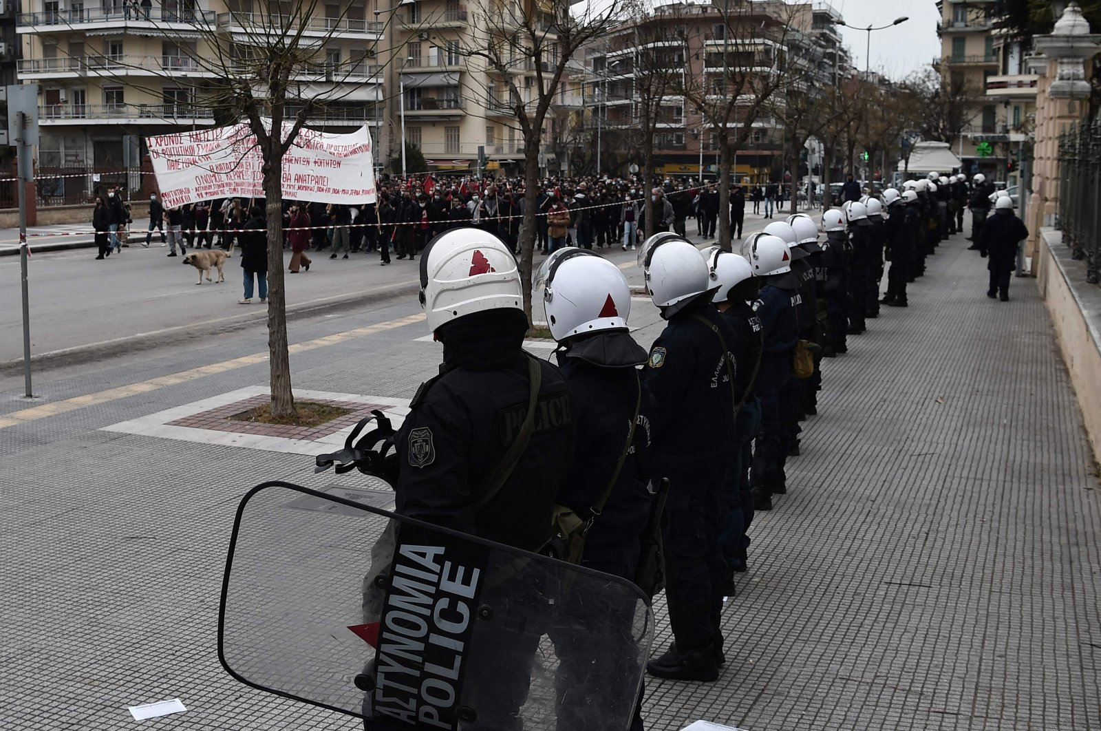 Greek anti-riot forces watch Greek students shouting slogans against police brutality after evening clashes with security forces over bitter allegations of police violence, in Thessaloniki, Greece, March 10, 2021. (AFP Photo)