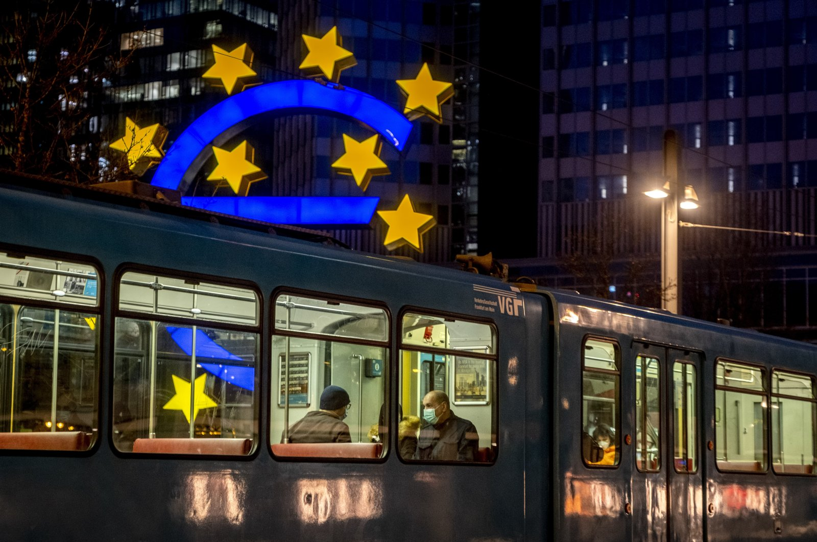People in a tram pass the Euro sculpture in Frankfurt, Germany, March 11, 2021. (AP Photo)