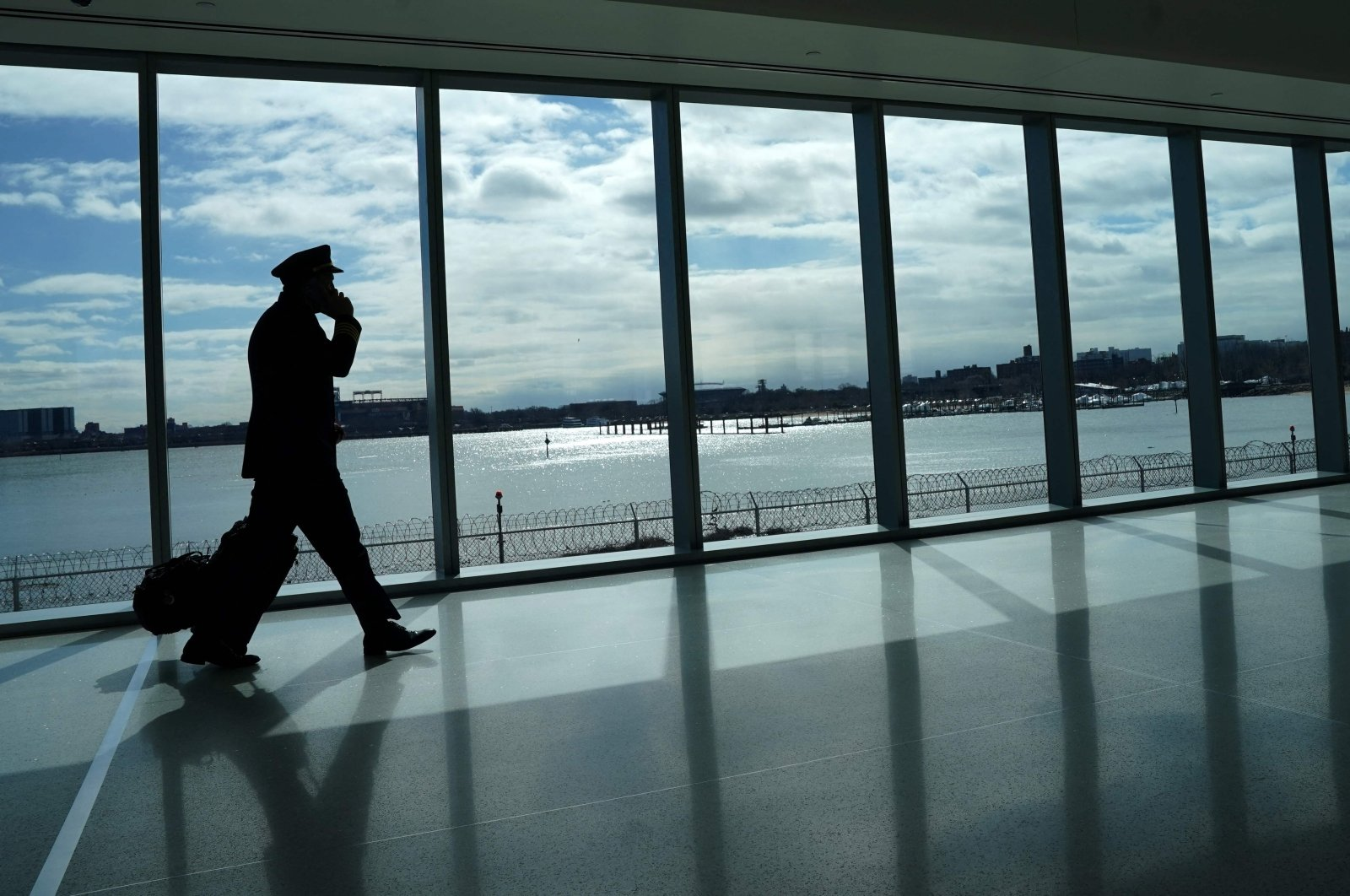 A pilot walks past the windows at LaGuardia Airport in New York, the U.S., March 6, 2021. (AFP Photo)