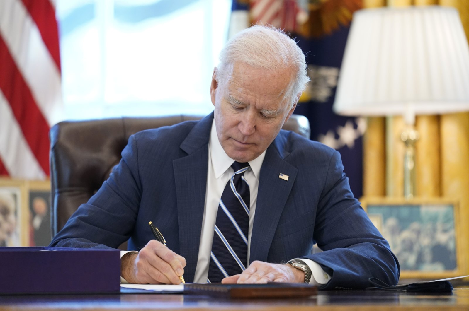 President Joe Biden signs the American Rescue Plan, a coronavirus relief package, in the Oval Office of the White House, in Washington, the U.S, March 11, 2021. (AP Photo)