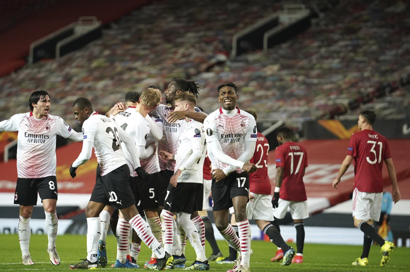 AC Milan players celebrate after Simon Kjaer scored Milan side's opening goal during the Europa League round of 16 first leg football match between Manchester United and AC Milan at Old Trafford in Manchester, England, March 11, 2021. (AP Photo)