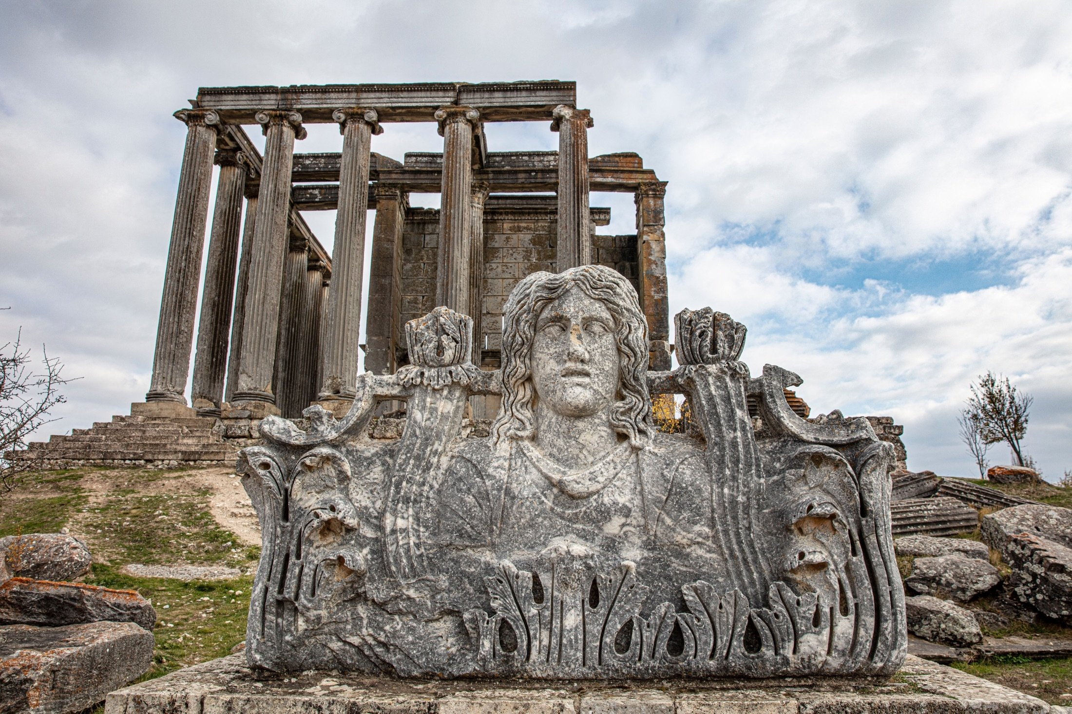 A sculpture can be seen with the ruins of the Zeus Temple in the background at the ancient city of Aizanoi in Kütahya, Turkey. (Shutterstock Photo)
