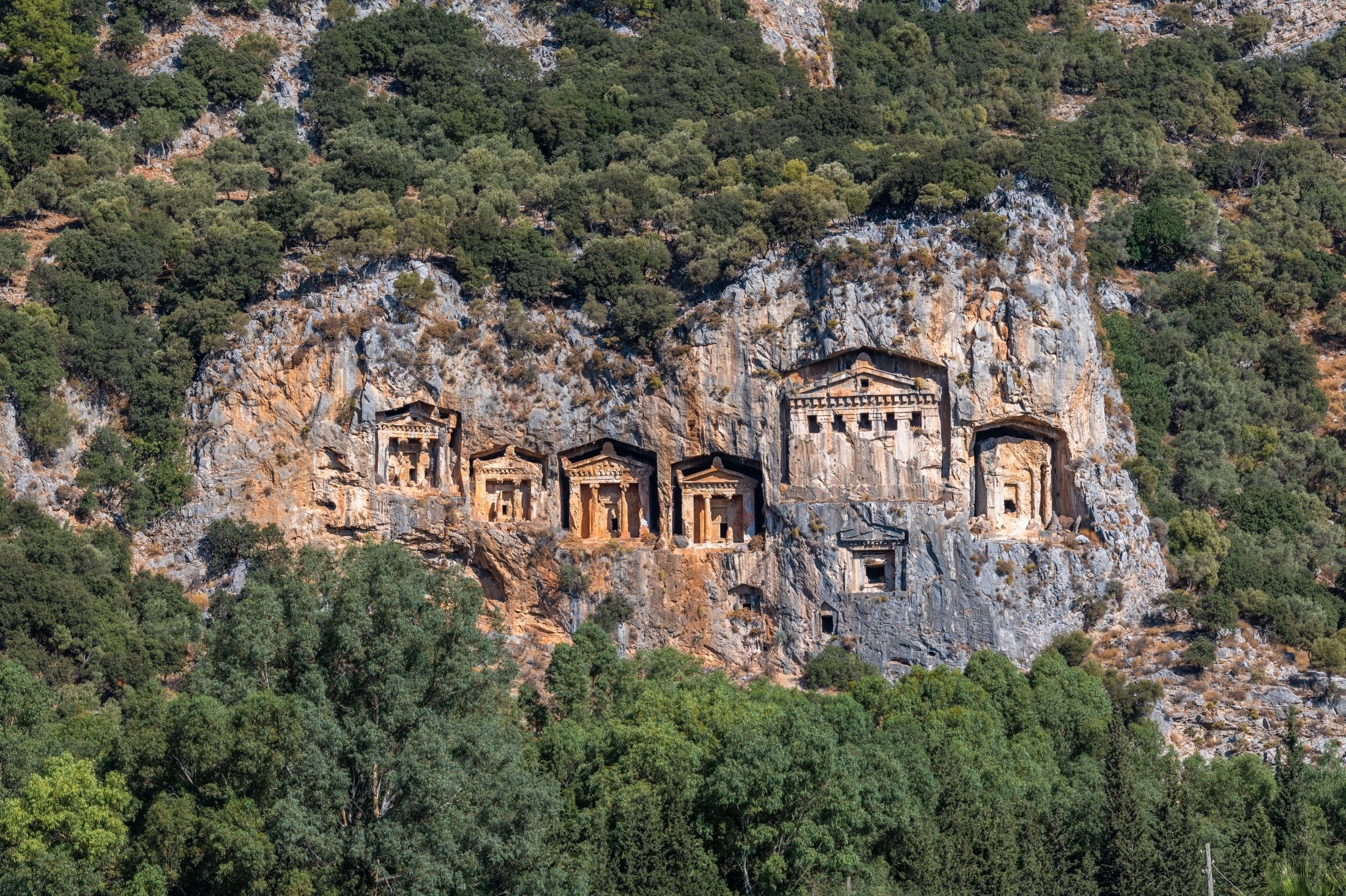 "Lycian rock tombs sculpted into the mountain side, called the ""Kings Tombs"" of the ancient city of Kaunos, can be seen in modern-day Dalyan, Muğla, southwestern Turkey. (Shutterstock Photo)"