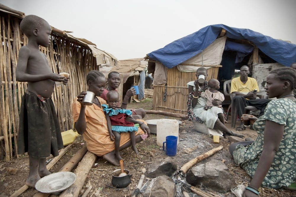 People have breakfast in front of their huts in a camp for the displaced, Juba, South Sudan, Feb. 28, 2012. (Shutterstock Photo)