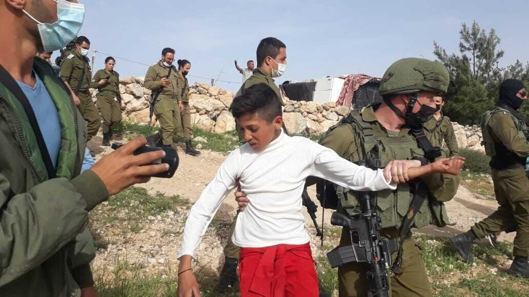 An Israeli soldier drags Palestinian boy as he detains him and four other children near a settlement outpost in Havat Maon, occupied West Bank, Palestine, March 11, 2021. (AA Photo)