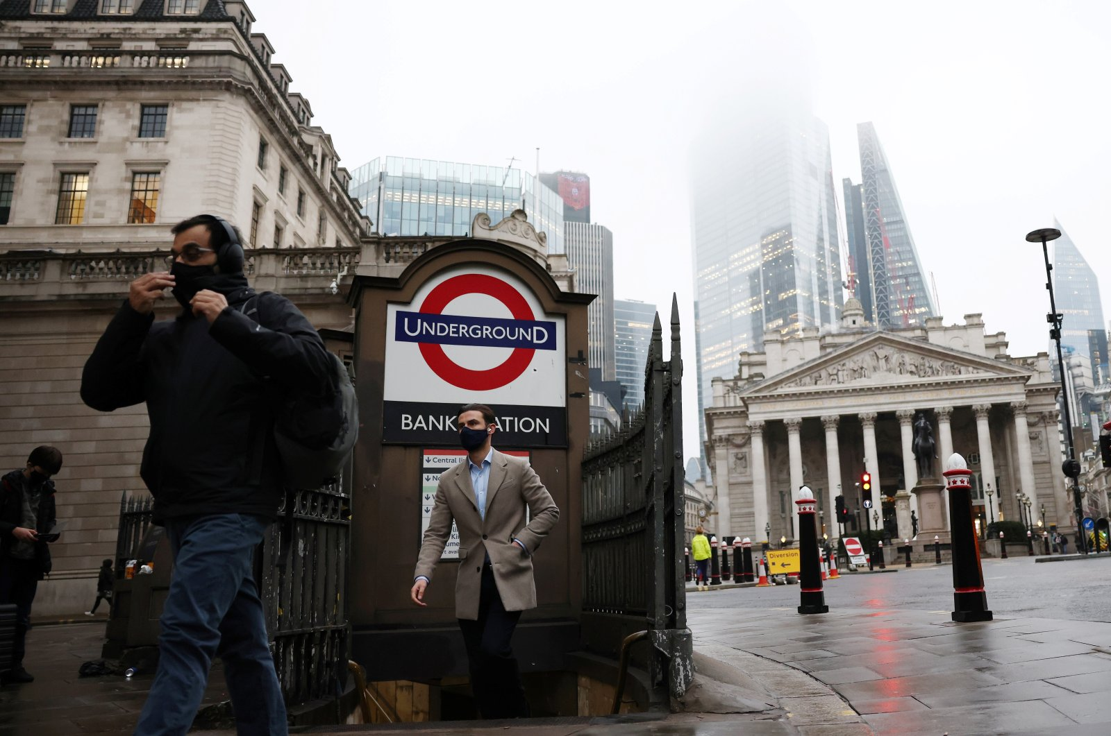 People exit Bank station in the City of London financial district, amid the coronavirus outbreak, in London, Britain, March 4, 2021. (Reuters Photo)